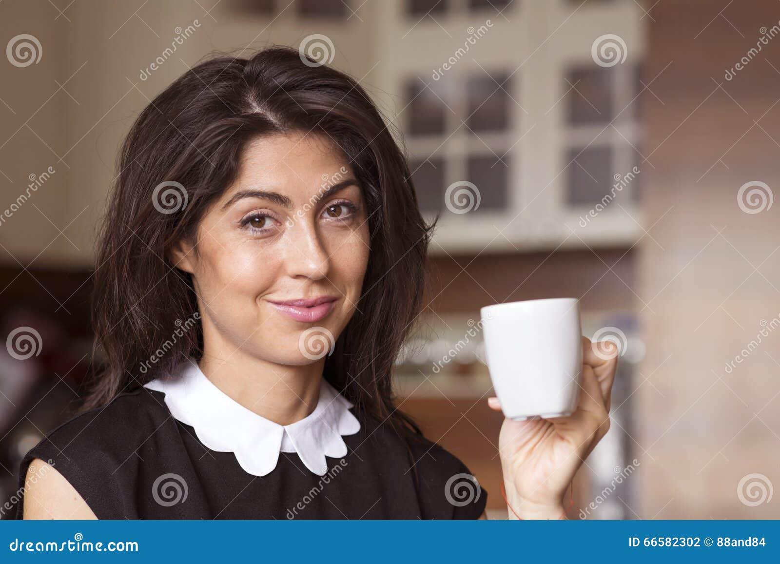 Schöne junge Frau, die zu Hause, trinkender Kaffee sitzt
