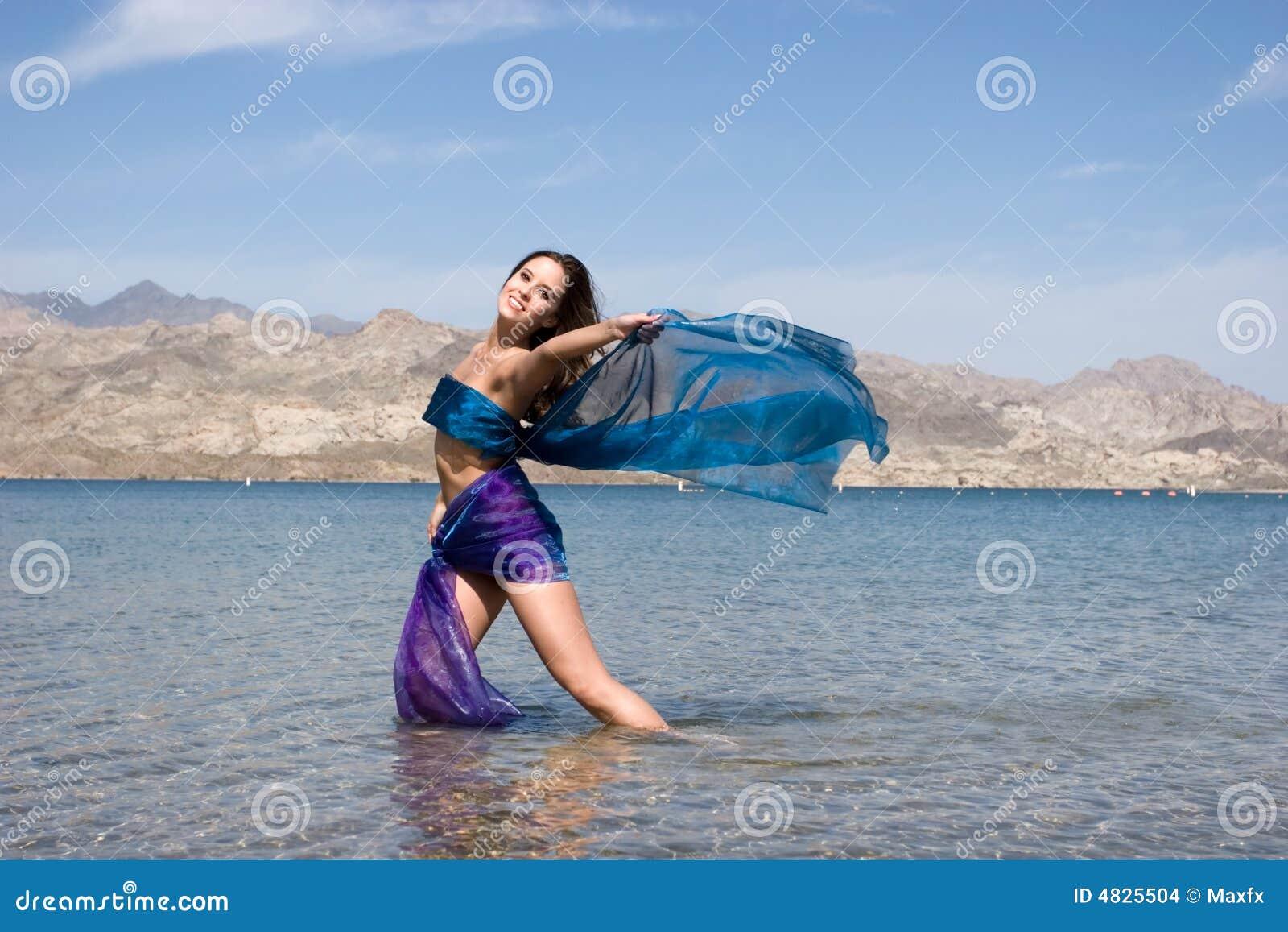 Schöne junge Frau durch den Strand