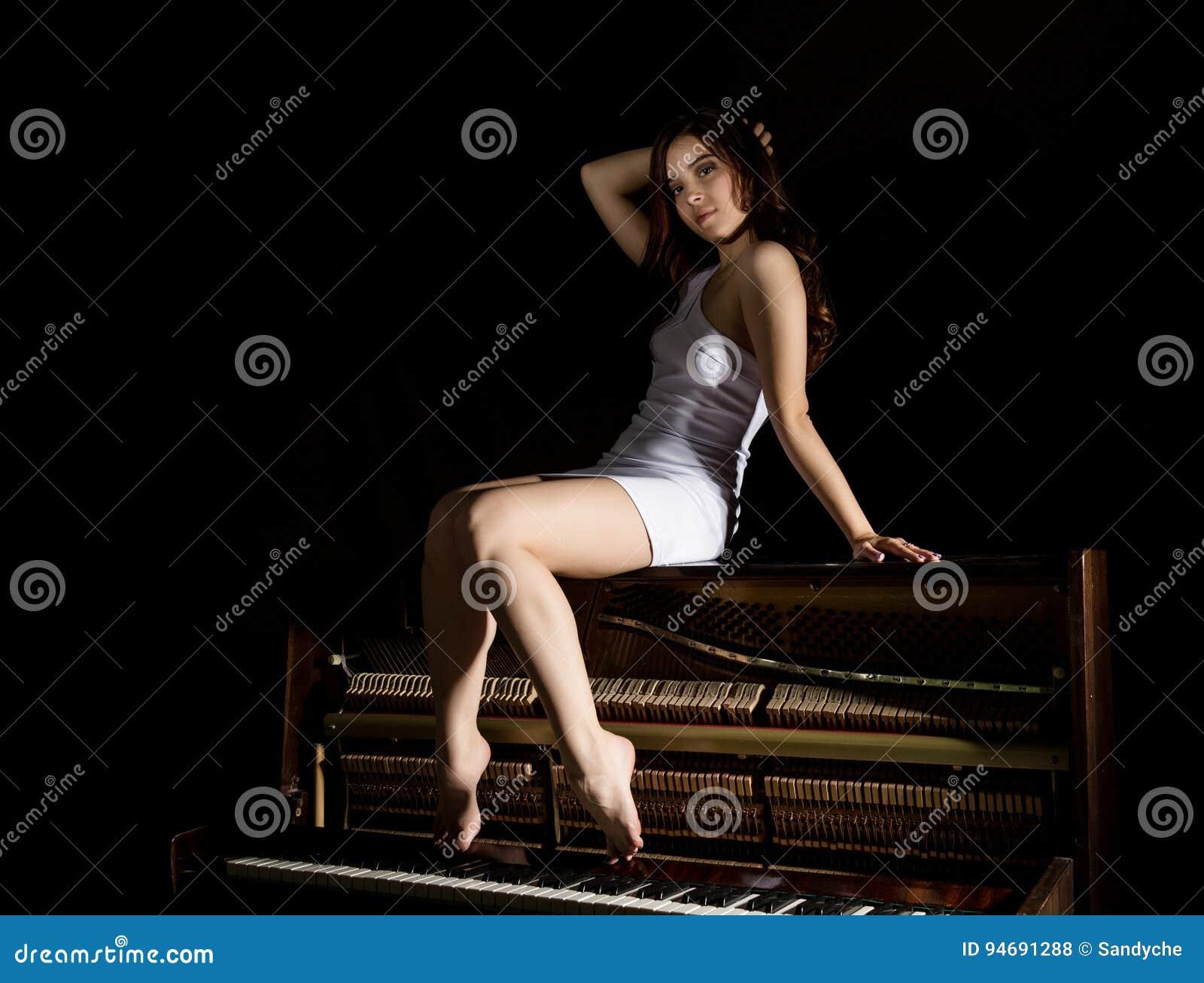 sch ne junge frau in einem wei en kleid mit einem offenen r cken der auf einem alten klavier. Black Bedroom Furniture Sets. Home Design Ideas