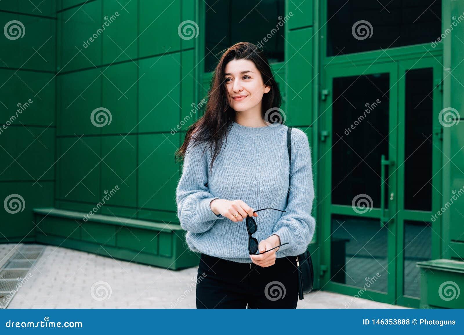 Schöne junge Frau in einer blauen Wollstrickjacke, die in der Stadtstraße auf städtischem Hintergrund des grünen Gebäudes aufwirf