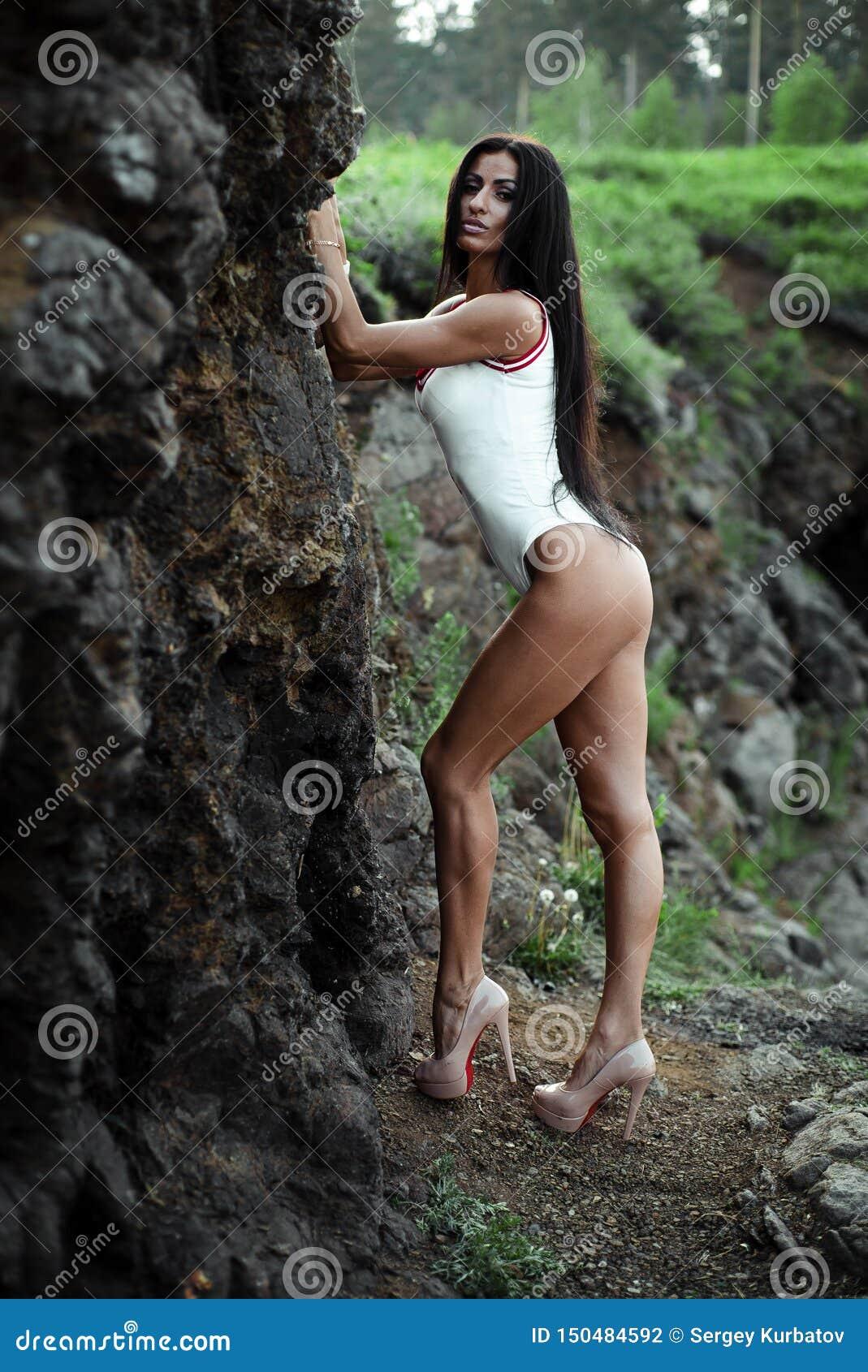 Schöne junge Frau im weißen Bodysuit mit den Fersen, die auf Steinhintergrund aufwerfen outdoor Gr?n