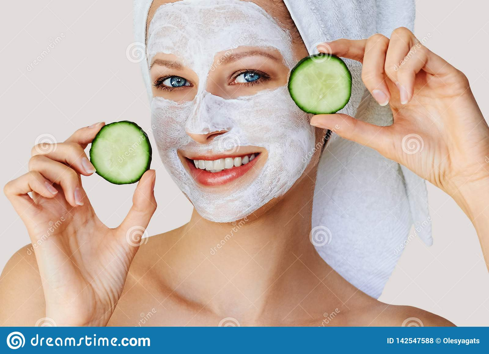 Schöne junge Frau mit Gesichtsmaske auf ihrem Gesicht, das Scheiben der Gurke hält Hautpflege und Behandlung, Badekurort, Natursc