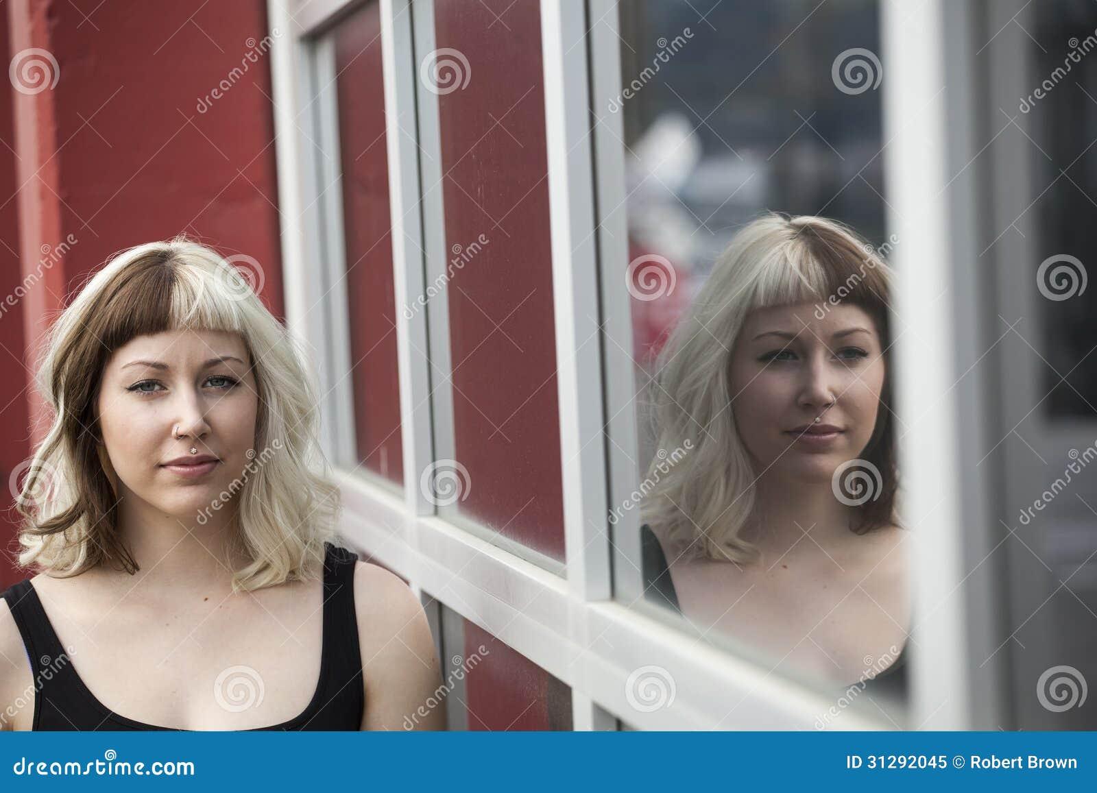 Schöne junge Frau mit ihrer Reflexion