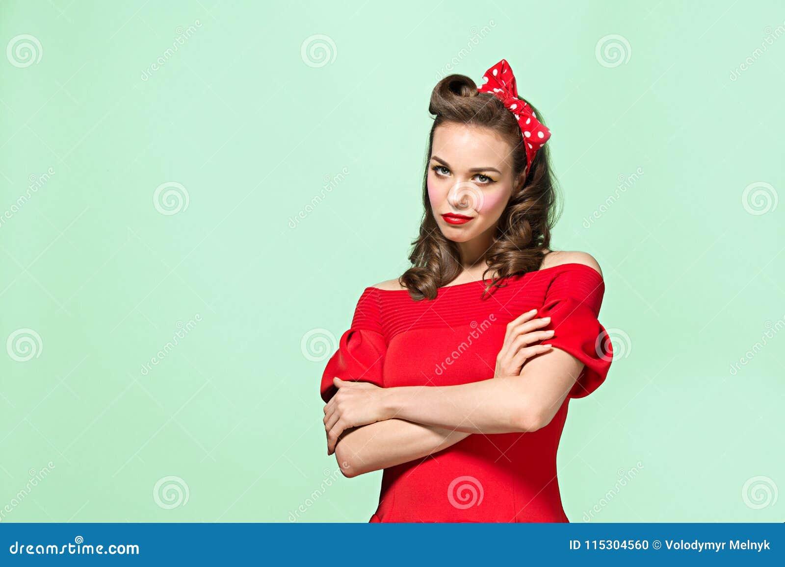 Schöne junge Frau mit Pinupmake-up und -frisur Atelieraufnahme auf weißem Hintergrund