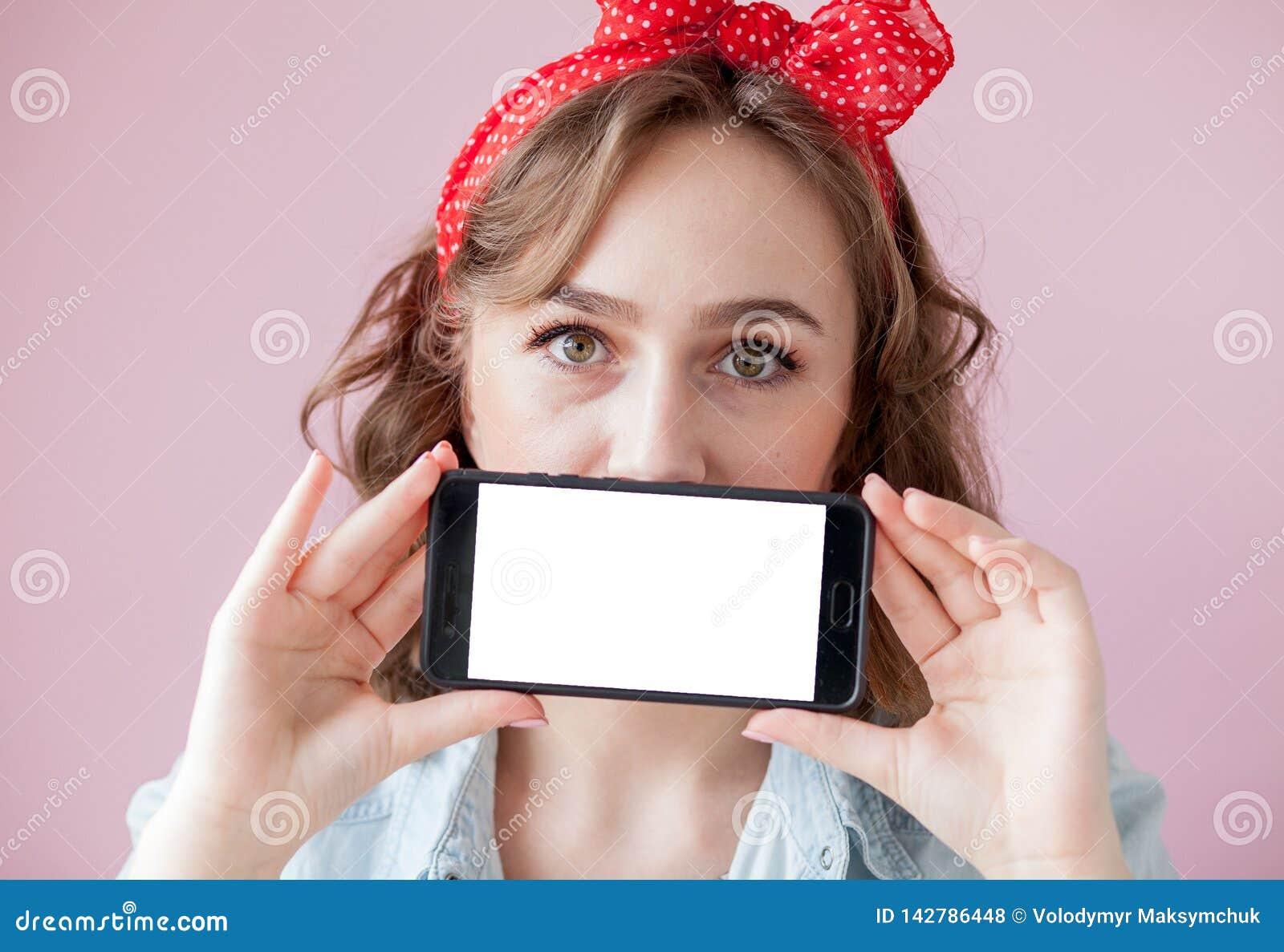 Schöne junge Frau mit Stift-obenmake-up und -frisur über rosa Hintergrund mit Handy mit Kopienraum