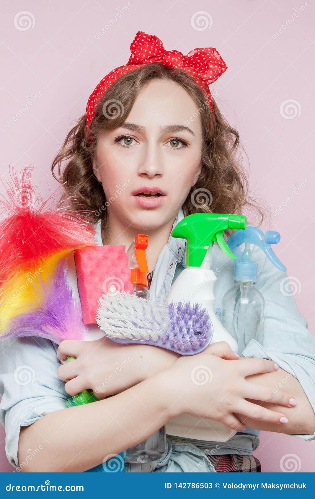 Schöne junge Frau mit Stift-obenmake-up und -frisur mit Reinigungswerkzeugen auf rosa Hintergrund