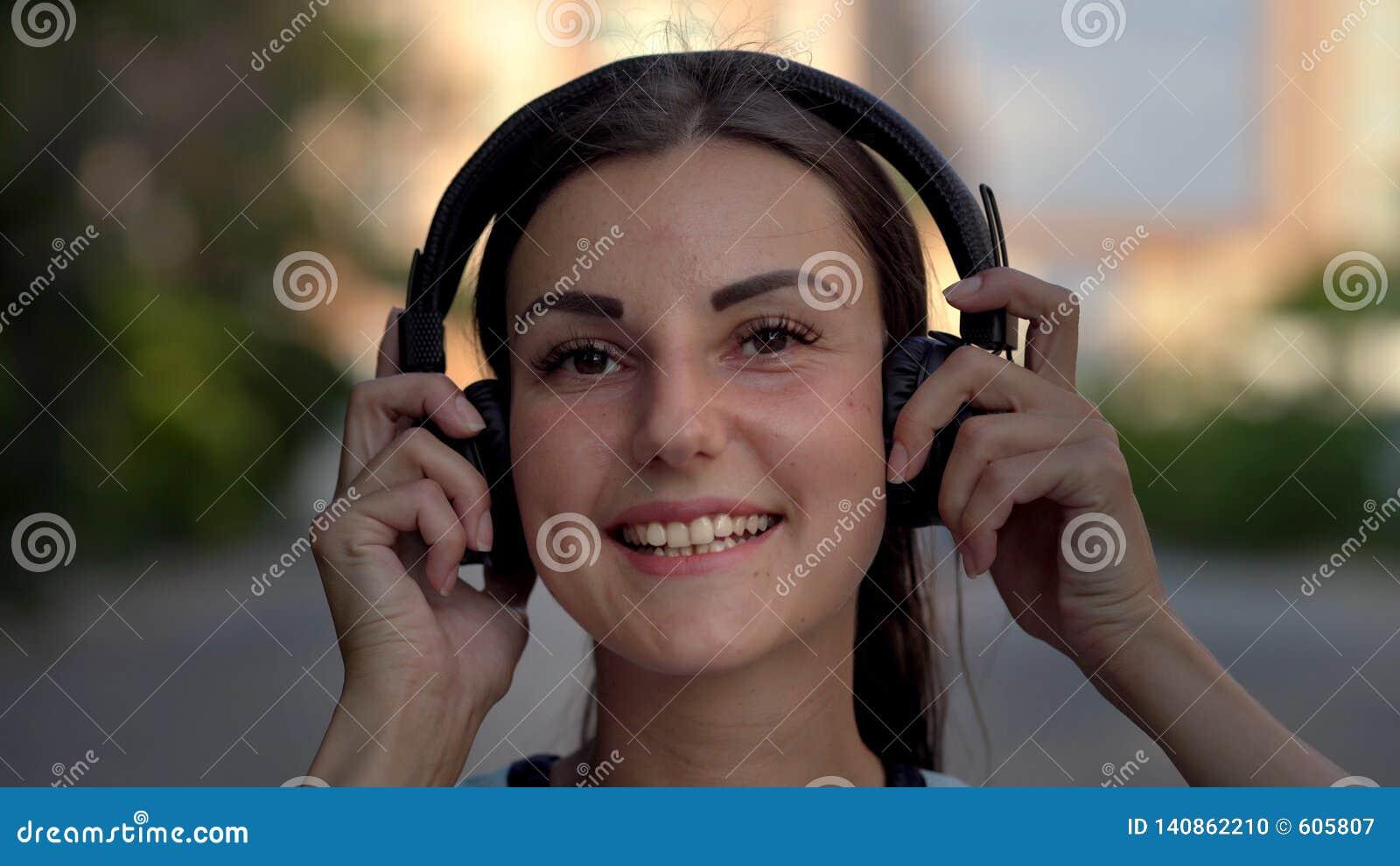 Schöne junge Frau unter Verwendung des intelligenten Telefons, Schreibenmitteilungen, hörend Musik, trinkender Kaffee beim Gehen
