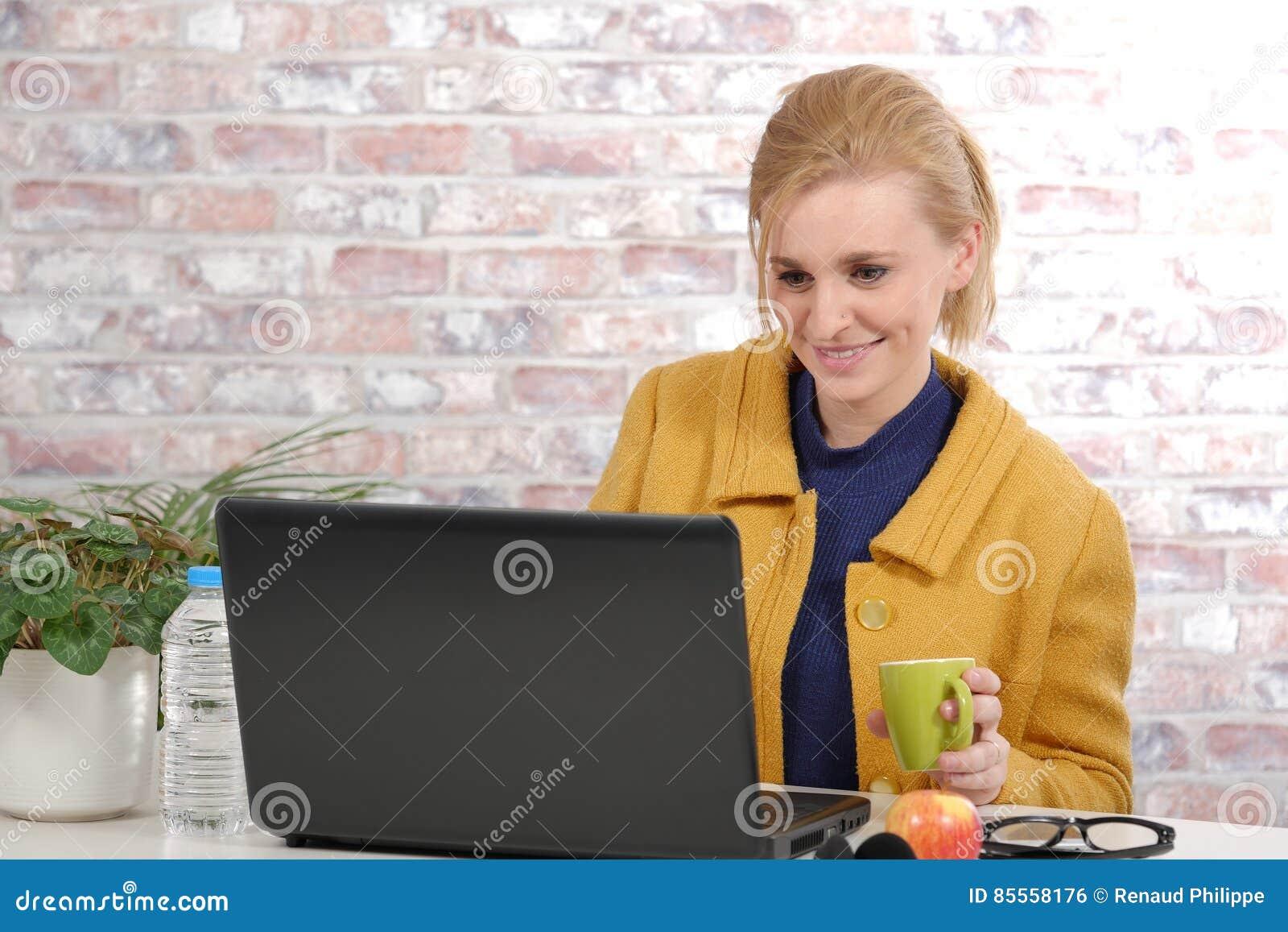 Schöne junge Geschäftsfrau mit einer gelben Jacke