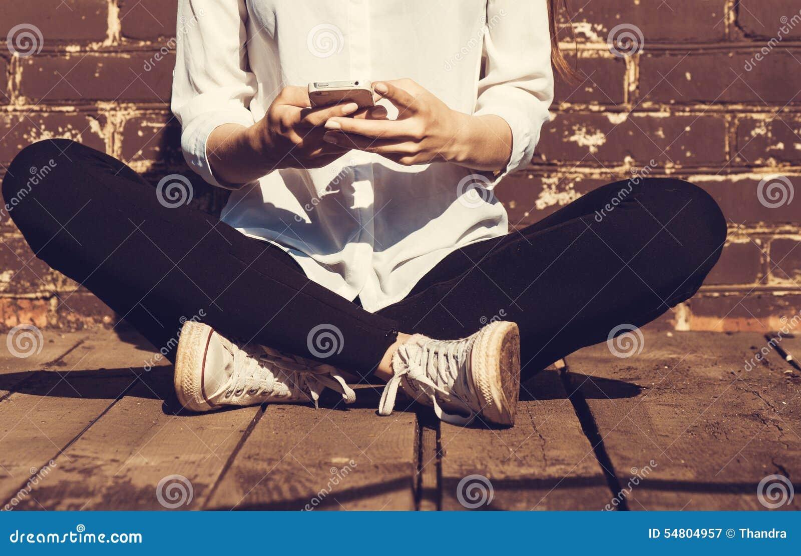 Schöne junge Hippie-Frau, die intelligentes Telefon verwendet