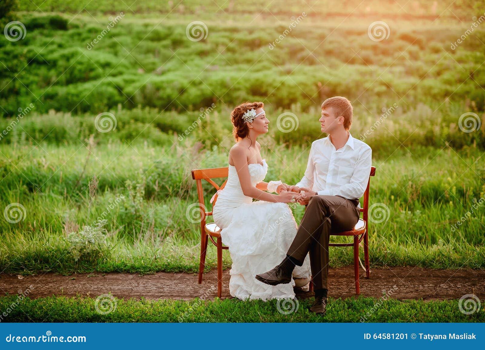 Schöne Junge Küssende Sitzende Stühle Der Braut Und Des Bräutigams Im  Sonnenuntergang Beleuchten