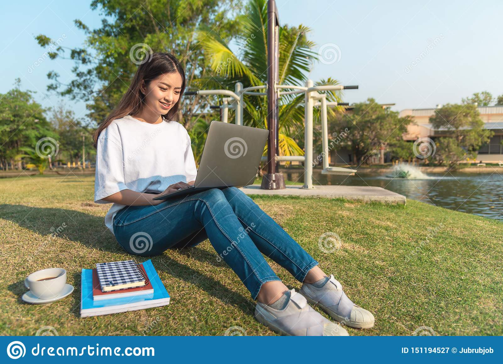 Schöne junge lächelnde Frau, die öffentlich Park der Tablette verwendet