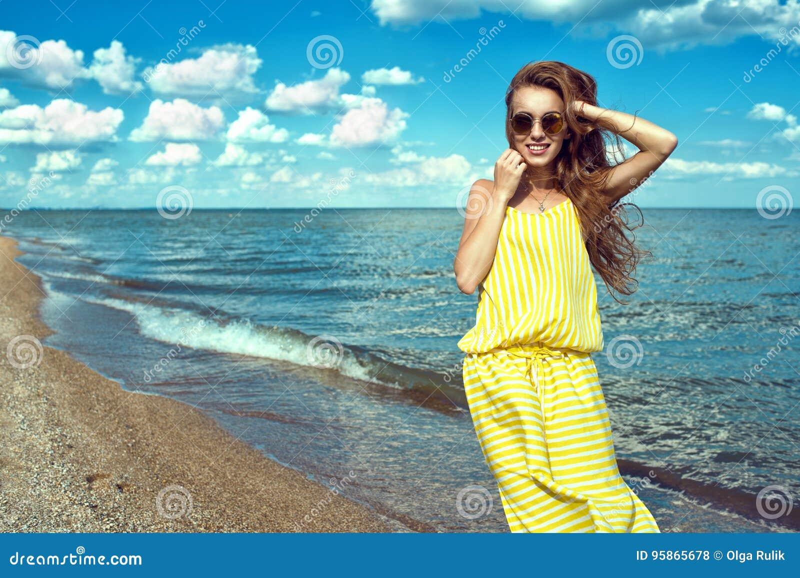 Schöne junge lächelnde Frau, die Maxi Kleid des gelben gestreiften sackartigen Sommers an der Küste trägt