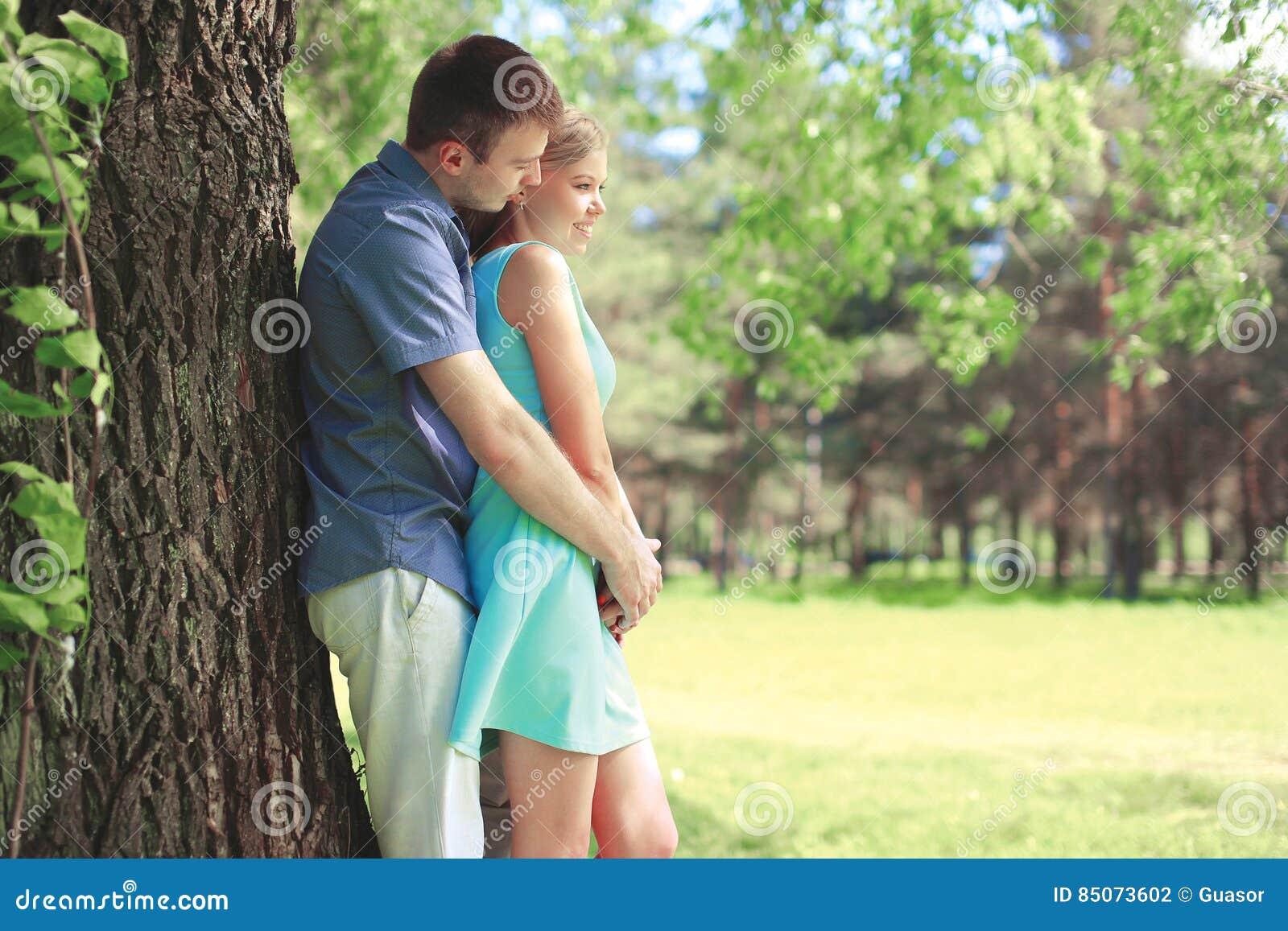Schöne junge Paare zusammen, Mann, der verliebte Frau am Sommerpark umarmt