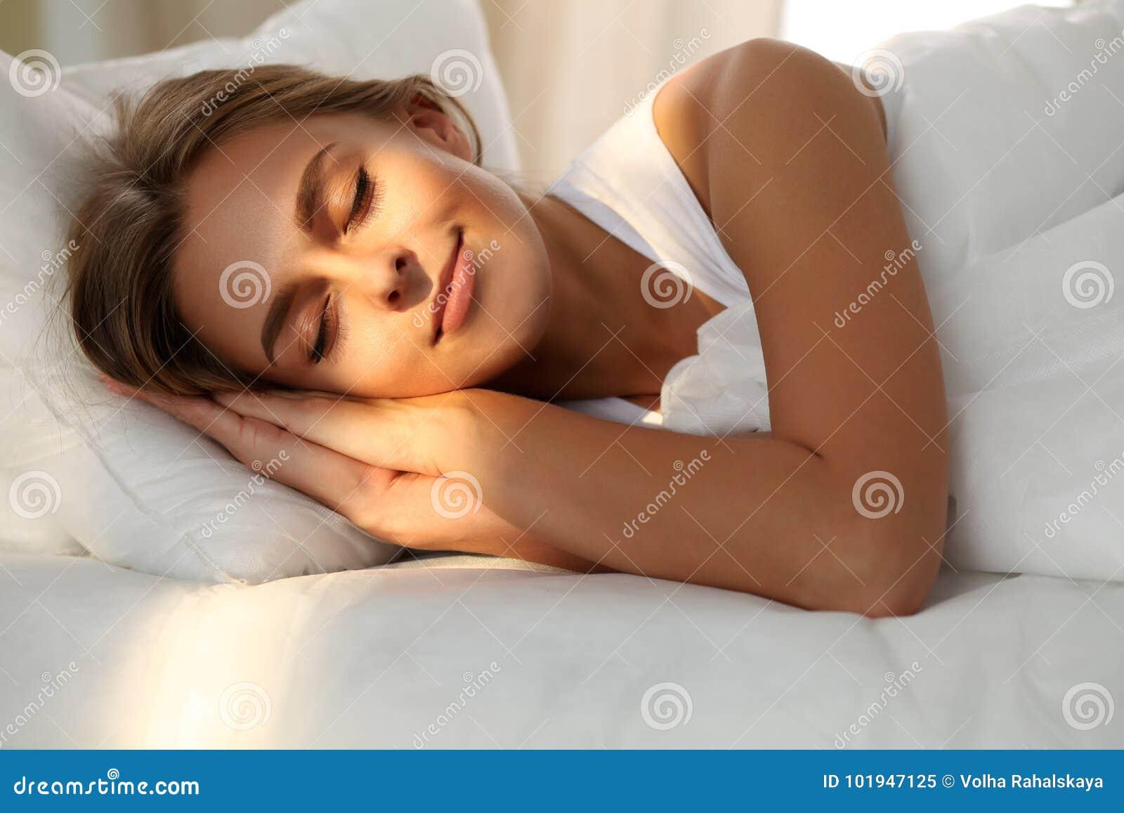 Schöne junge schlafende Frau beim im Bett bequem und himmlisch liegen Sonnenstrahldämmerung auf ihrem Gesicht
