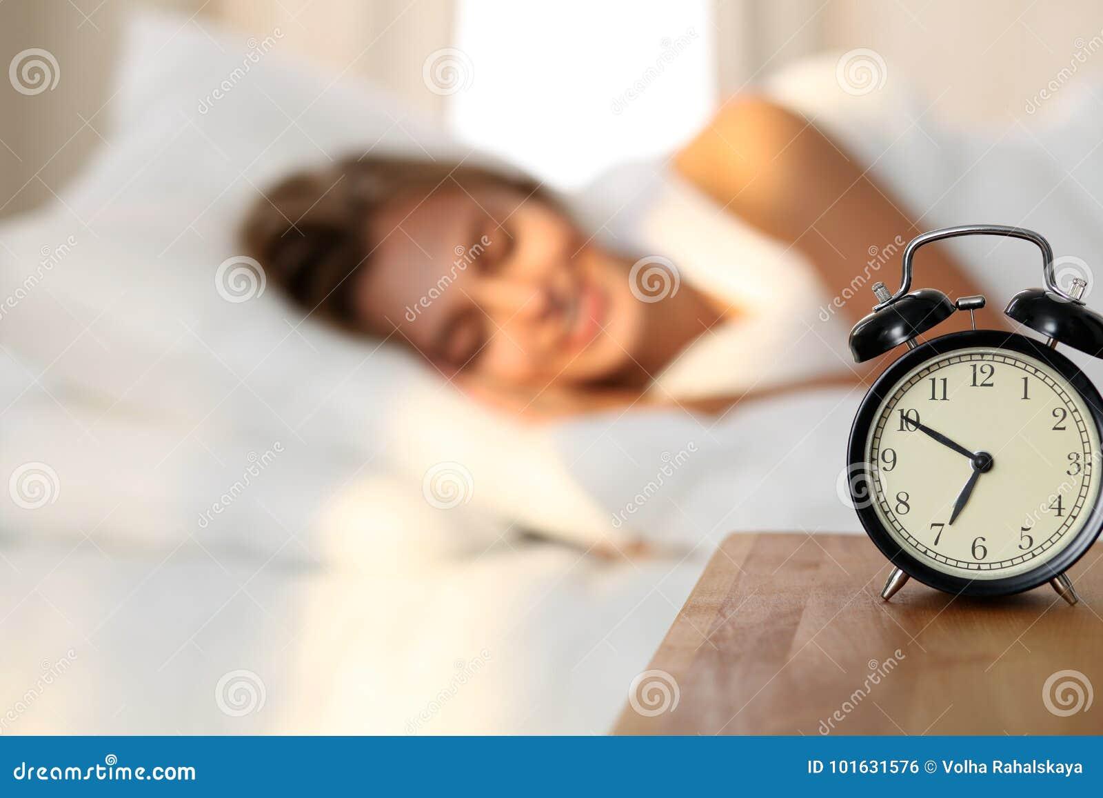 Schöne junge schlafende und beim im Bett auf dem Hintergrund der Warnung bequem und himmlisch liegen lächelnde Frau