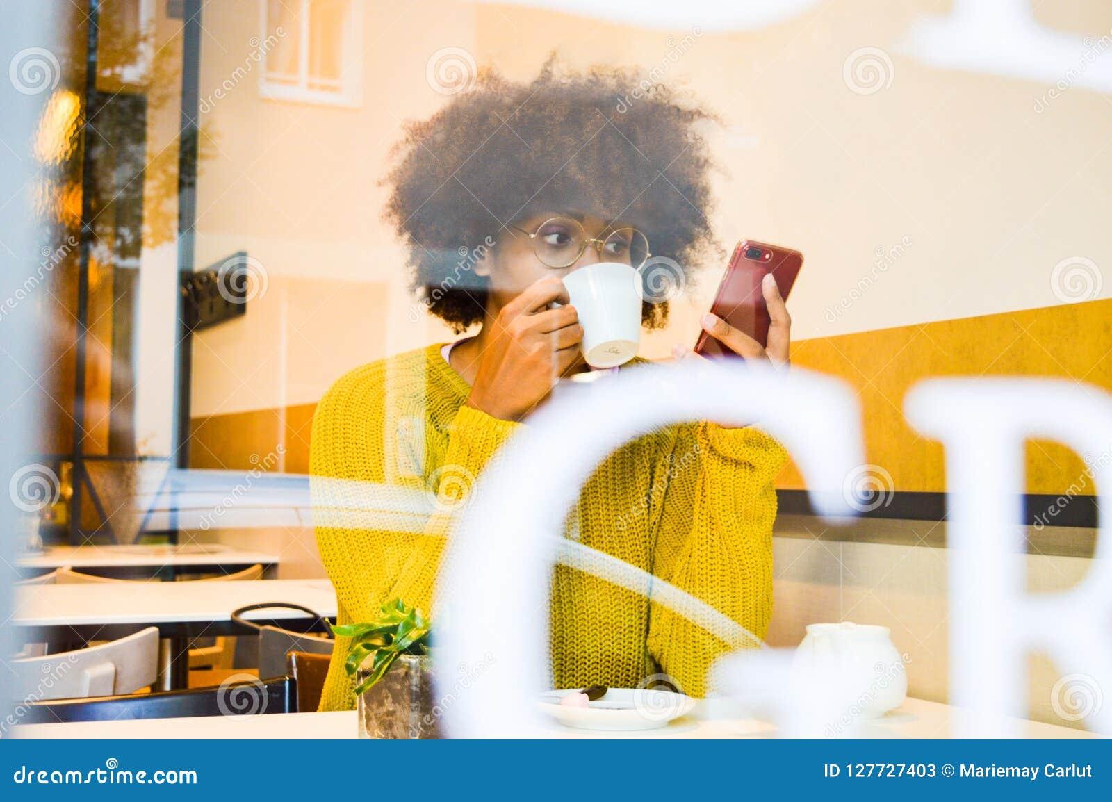 Schöne junge schwarze Frau, die den trinkenden Kaffee des Smartphone auf das Kaffeehaus betrachtet
