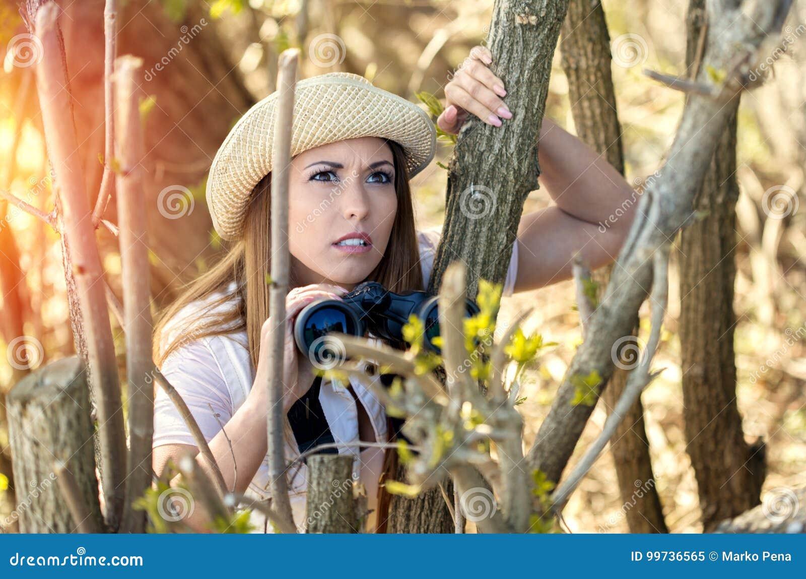 Schöne junge Wandererfrau, die im Wald etwas betrachtet