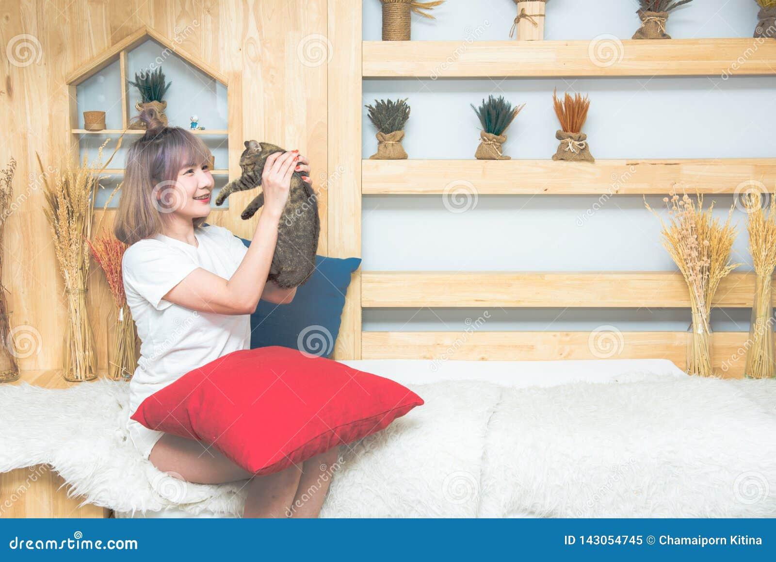 Schöne kaukasische Frau des glücklichen jungen Asiaten, die eine Katze küsst und hält Mit Haustier zu Hause spielen Liebe, Gemütl