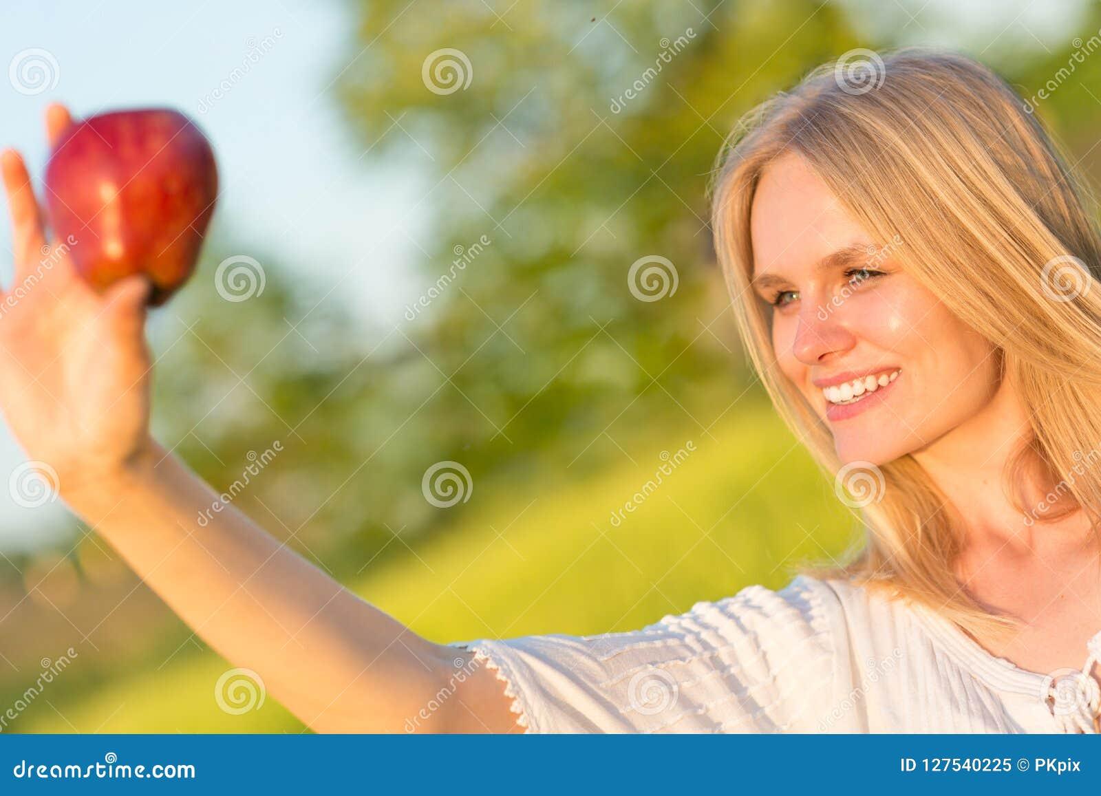 Schöne lächelnde Frau, die einen roten Apfel im Park isst Im Freiennatur