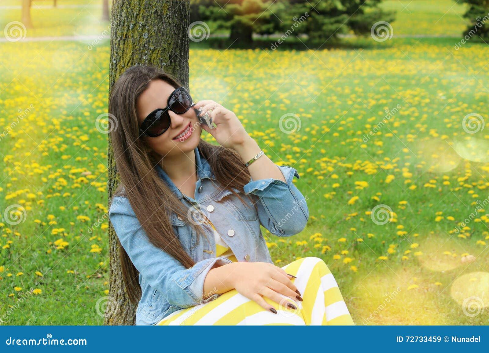 Schöne lächelnde Frau, die am Handy spricht