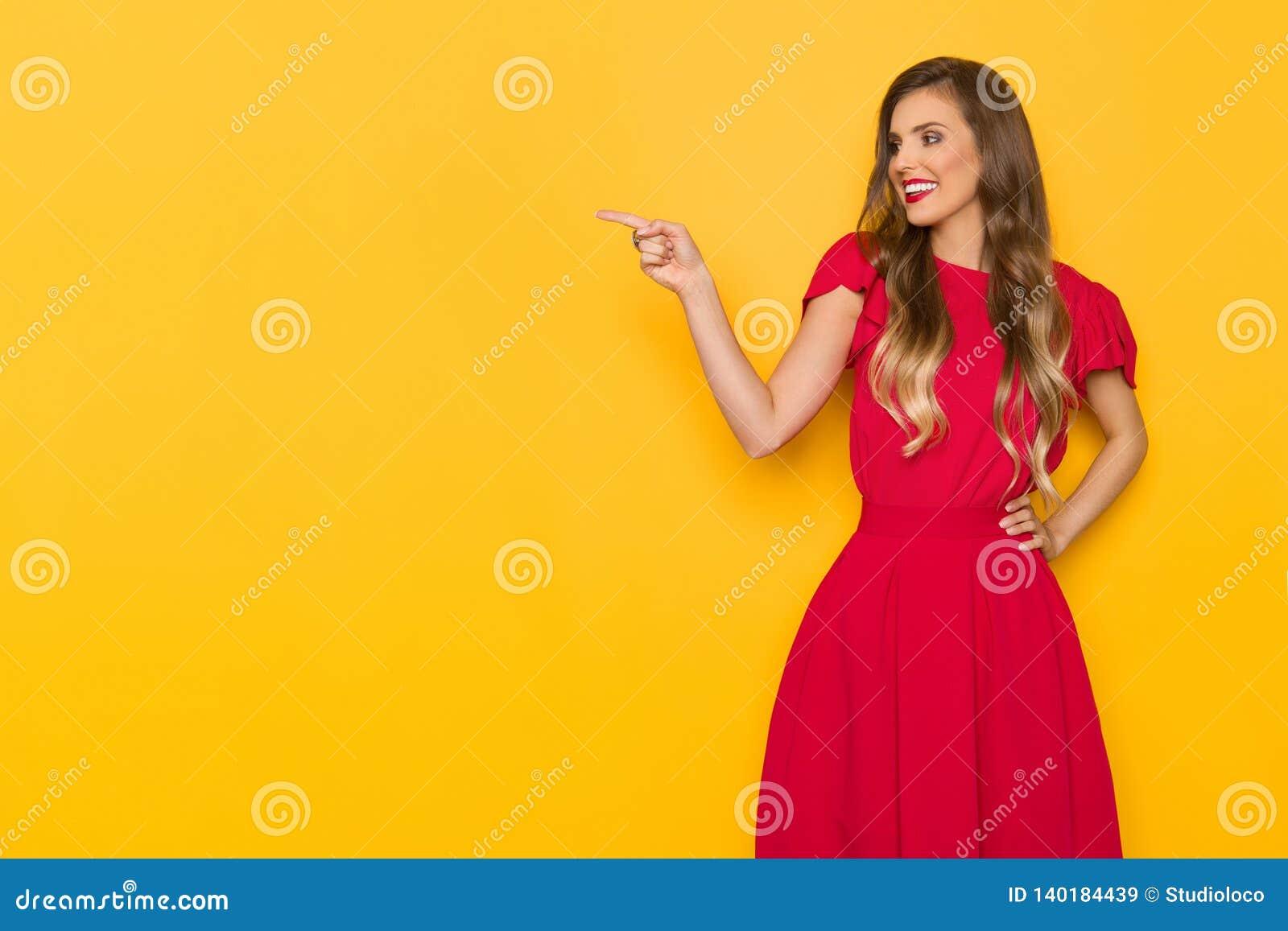 Schöne lächelnde junge Frau im roten Kleid ist weg zeigend und schauend