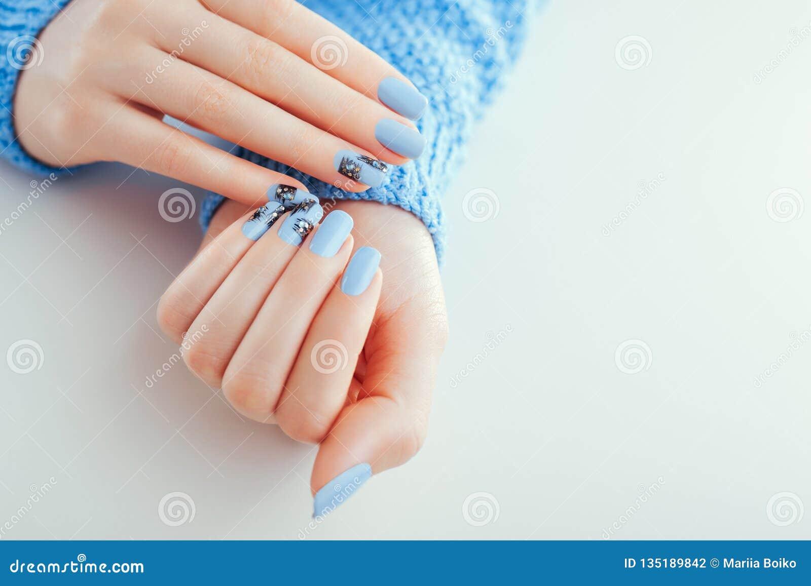 Schöne Maniküre des neuen Jahres Blaue Nägel mit schwarzem Entwurf und Bergkristallen platz