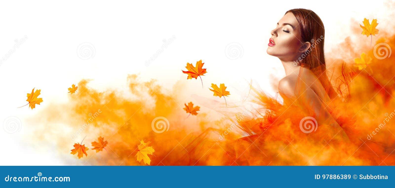 Schöne Modefrau im Herbstgelbkleid mit dem Fallen verlässt
