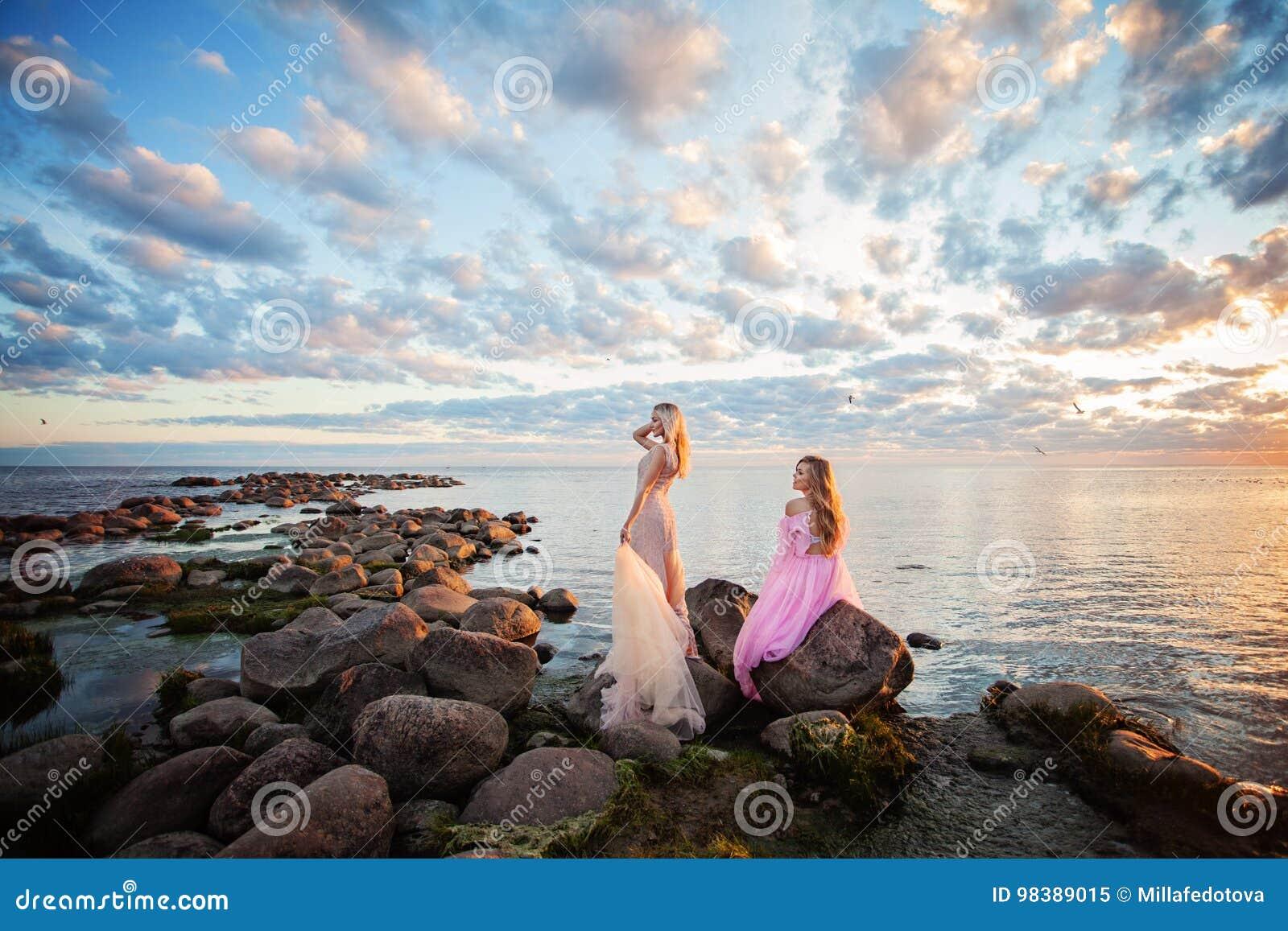 Schöne Modell-Frau auf Sonnenuntergang-Küste draußen