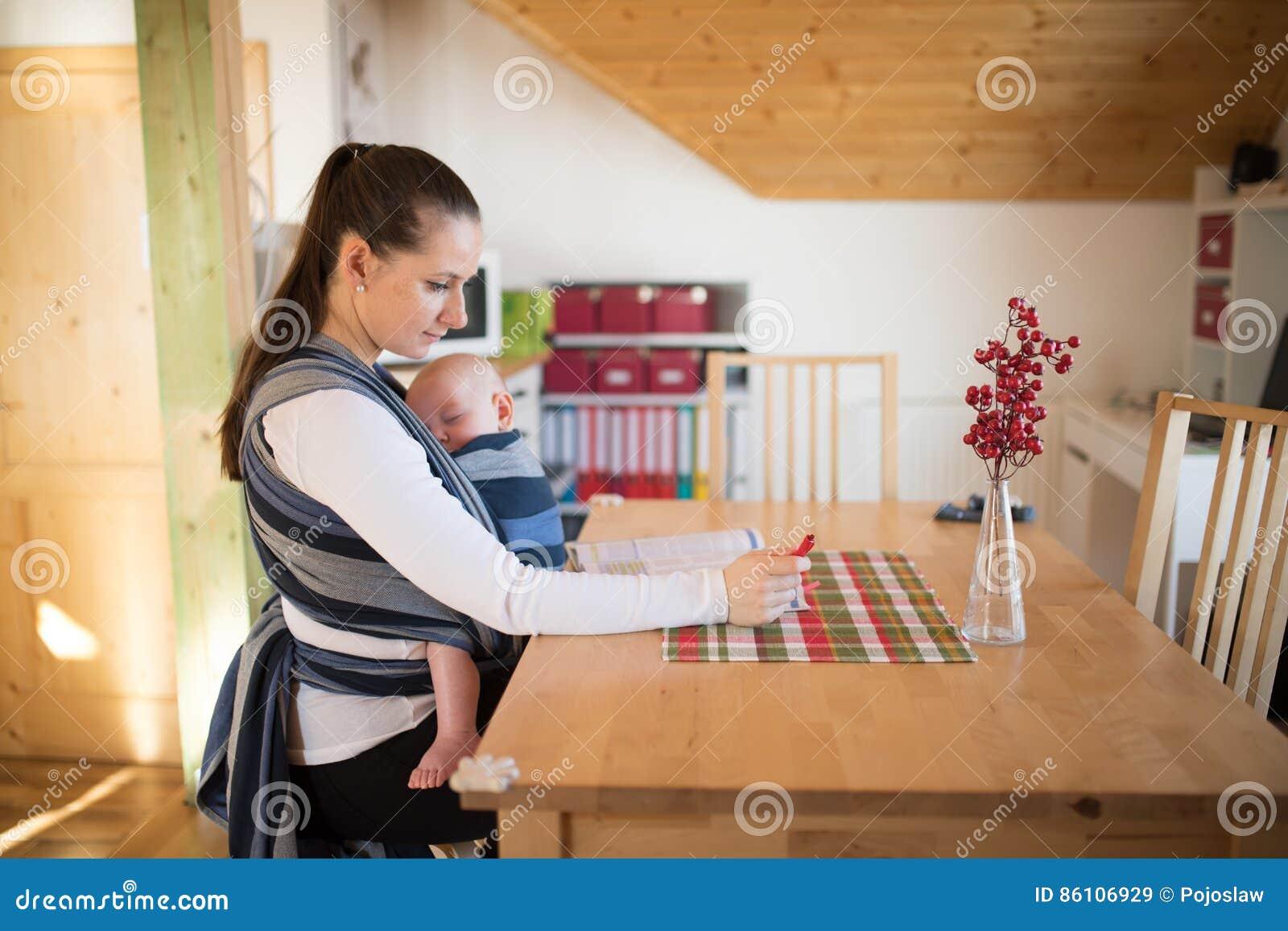 Schöne Mutter In Der Küche Mit Ihrem Sohn Der Im Riemen Schläft