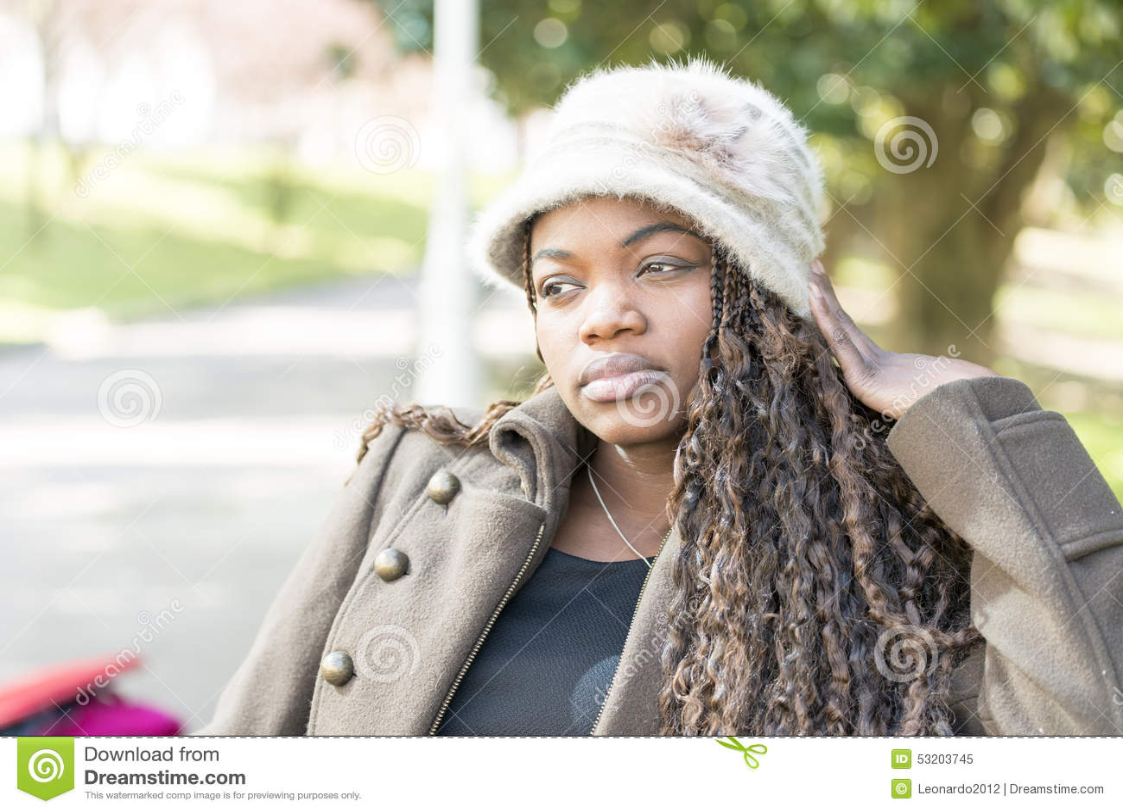 Schöne nachdenkliche afrikanische junge Frau mit Hut im Park