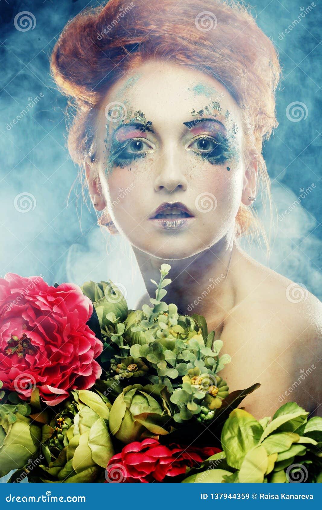 Schöne redhair Frau, die Blumen hält