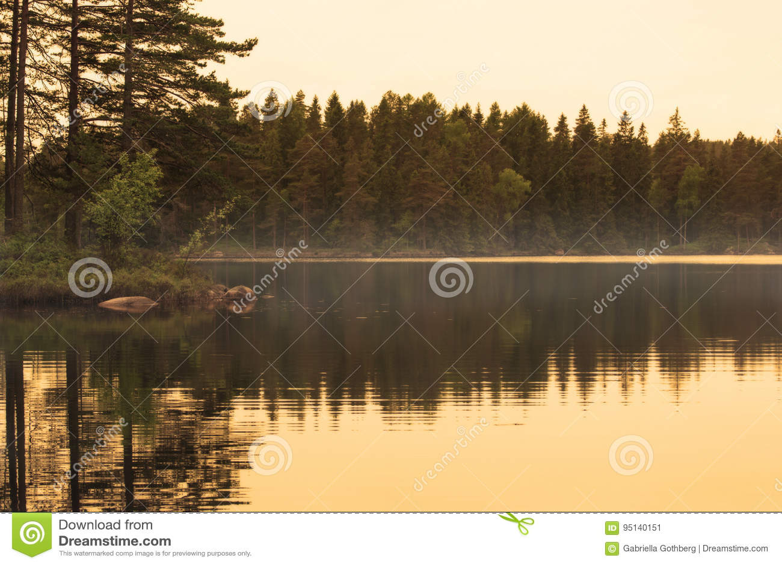 Schöne Reflexion der goldenen Stunde von Insel im nebelhaften See