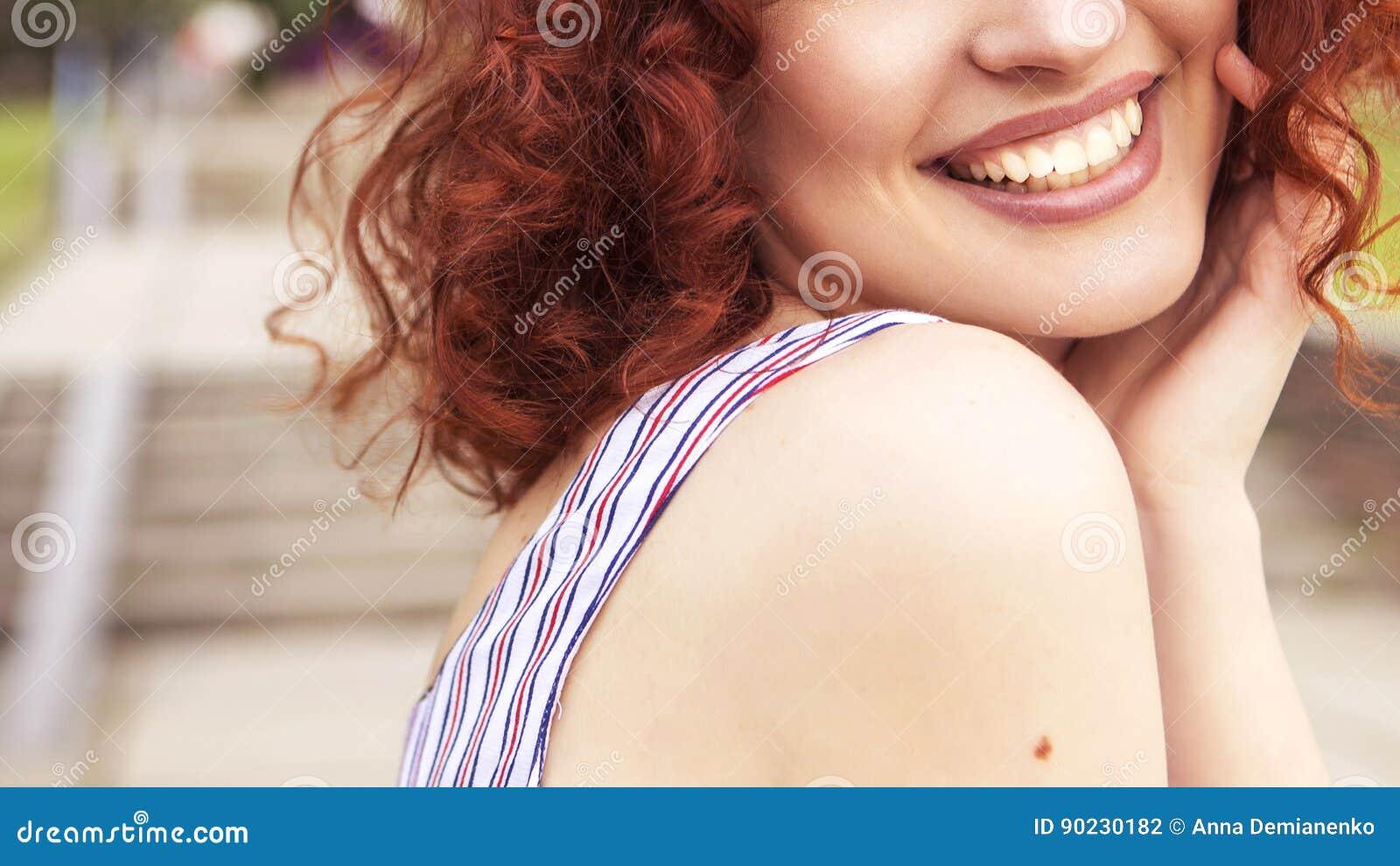 Schöne rote behaarte Frau mit frischer makelloser Haut und gelocktem ha