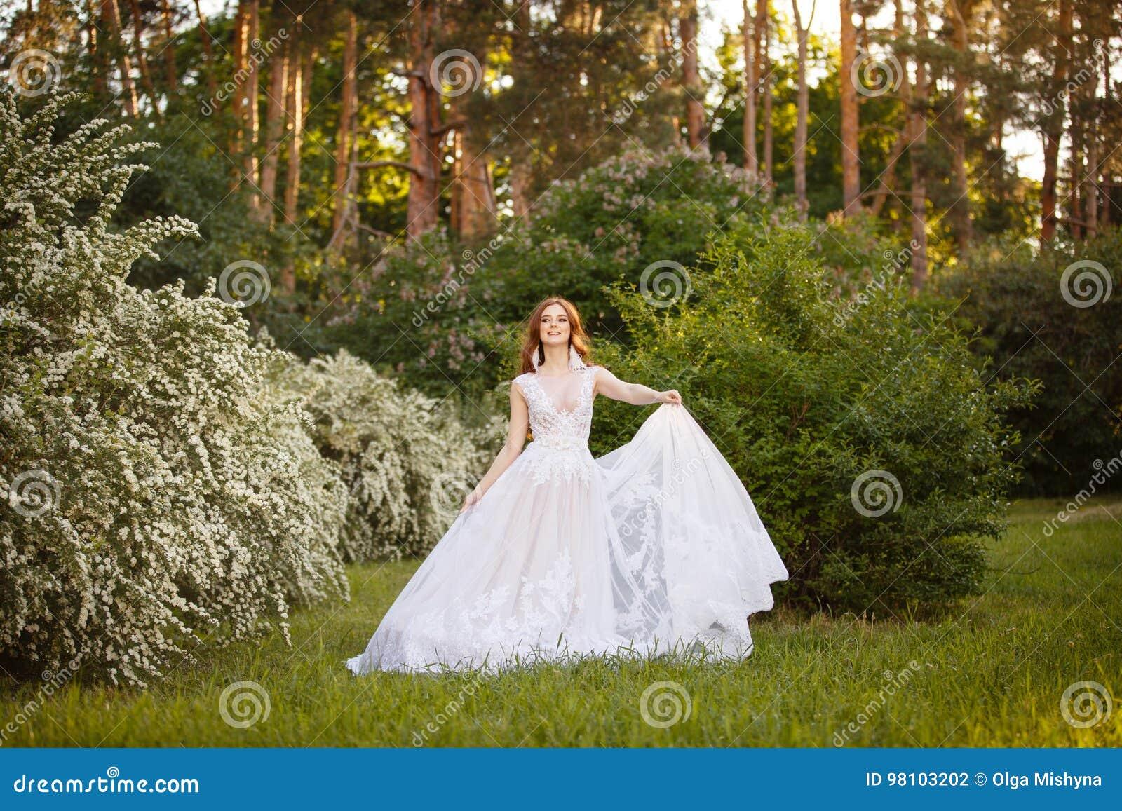 Schöne Rothaarige Braut im fantastischen Hochzeitskleid in blühendem Garten