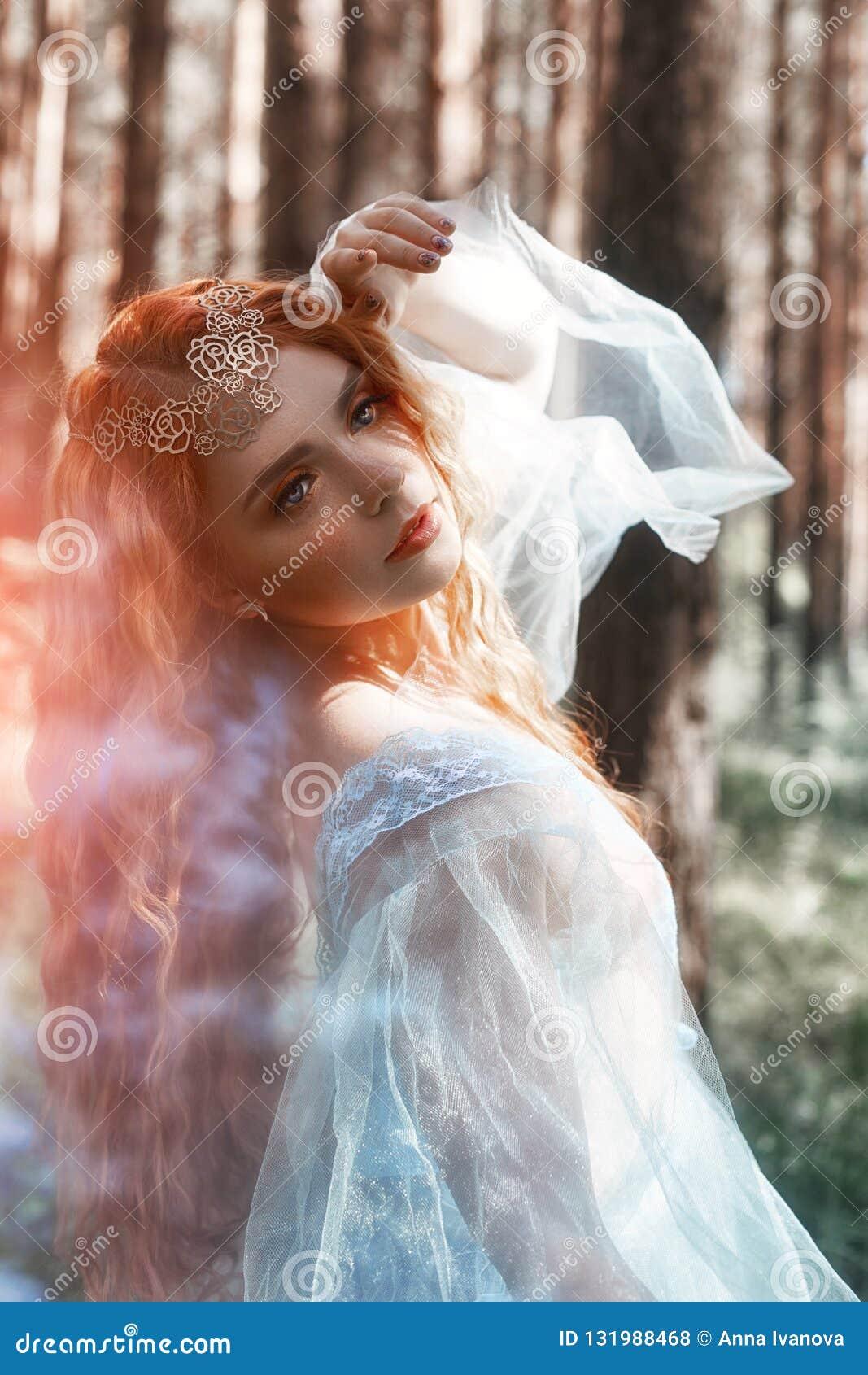 Schöne Rothaarigefrauen-Waldnymphe in einem blauen transparenten hellen Kleid im Wald, das in Tanz spinnt Rote Haarmädchen Kunstm
