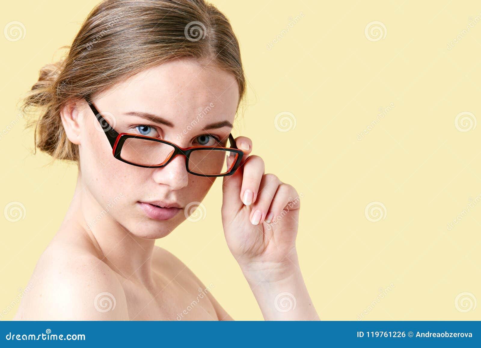 Schöne Rothaarigejugendliche mit den Sommersprossen, die Lesebrille tragen Junge Frau mit Gläsern