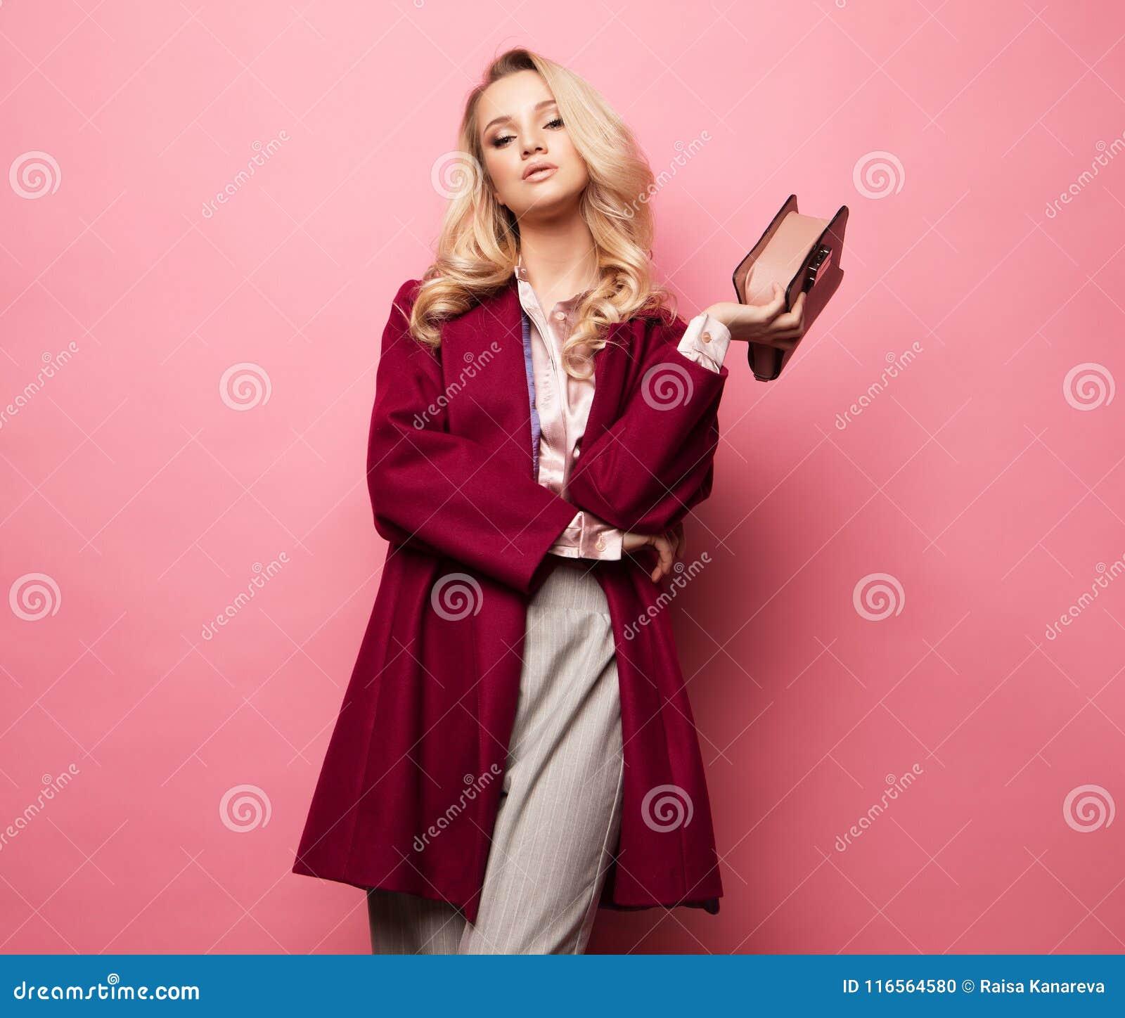 Schöne süße junge Frau, die in der netten Kleidung, roter Mantel, Handtasche aufwirft Frühlingsmodekonzept