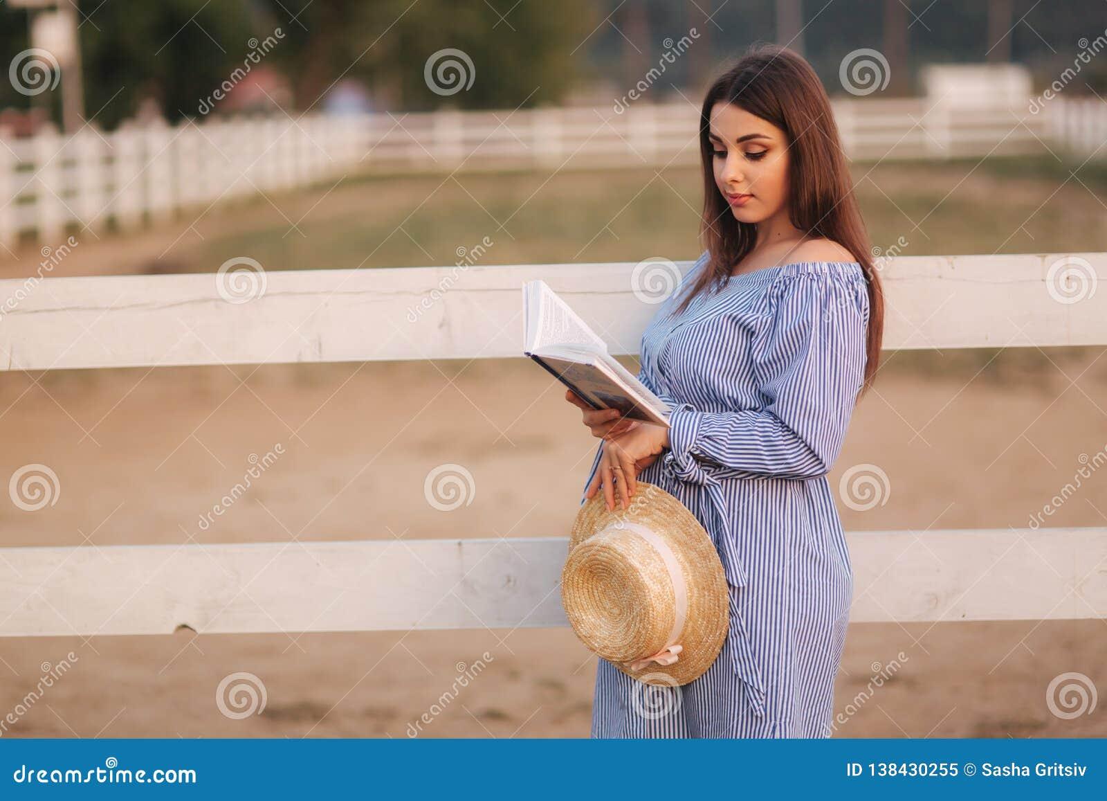Schöne schwangere Frau las das Buch auf dem Bauernhof Sie steht das fance bereit und schaut herein zum Buch relax