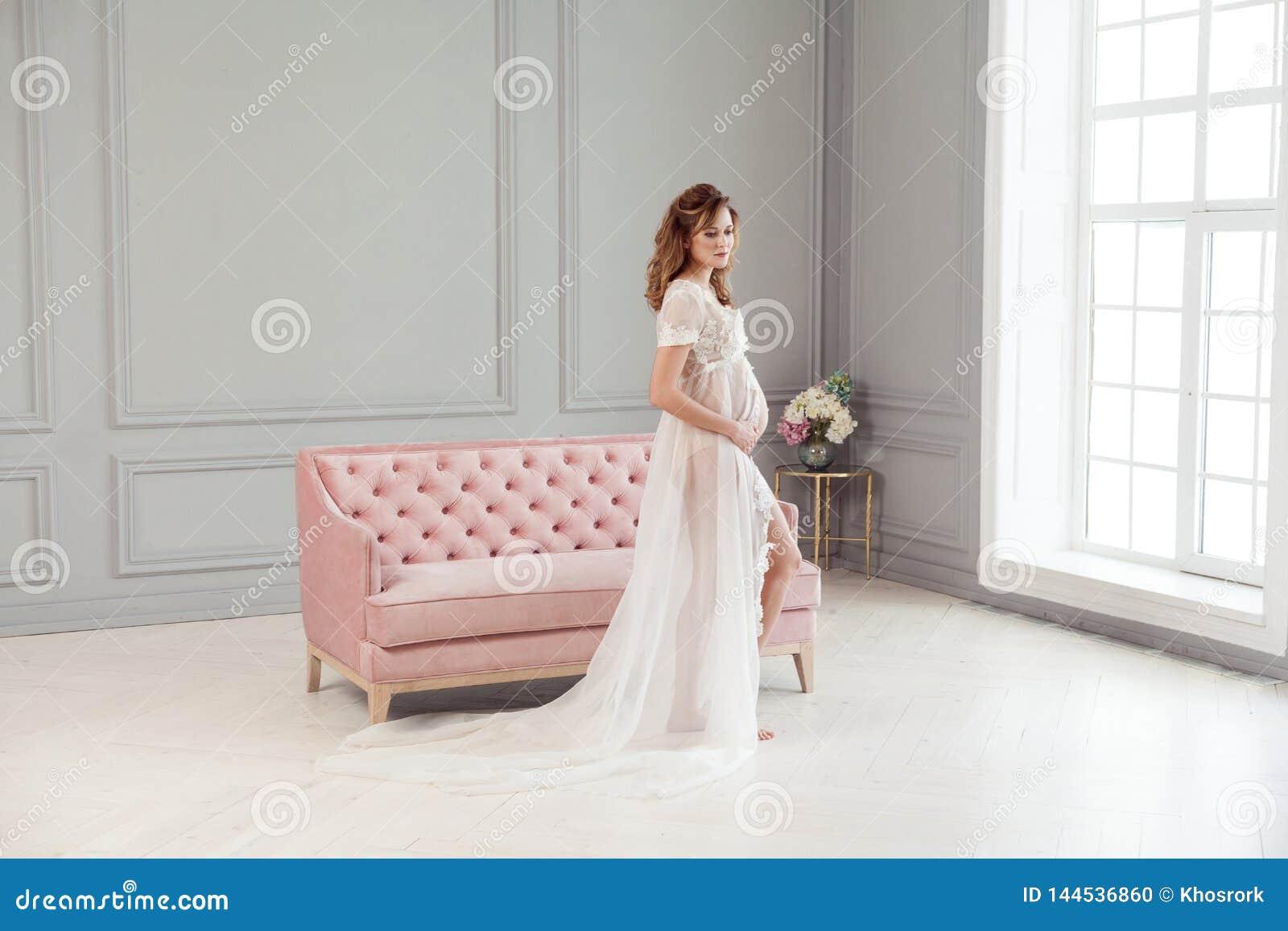 Schöne schwangere junge Frau im weißen Kleid-peignoir, das nahe dem rosa Sofa, mit Liebe ihren Bauch halten steht