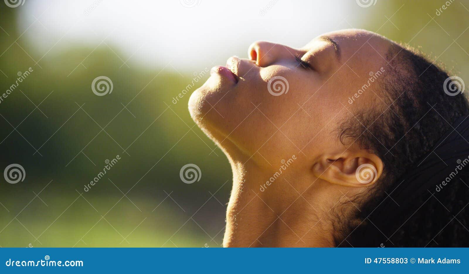 Schöne schwarze Frau, die der Sonne auf ihrem Gesicht glaubt