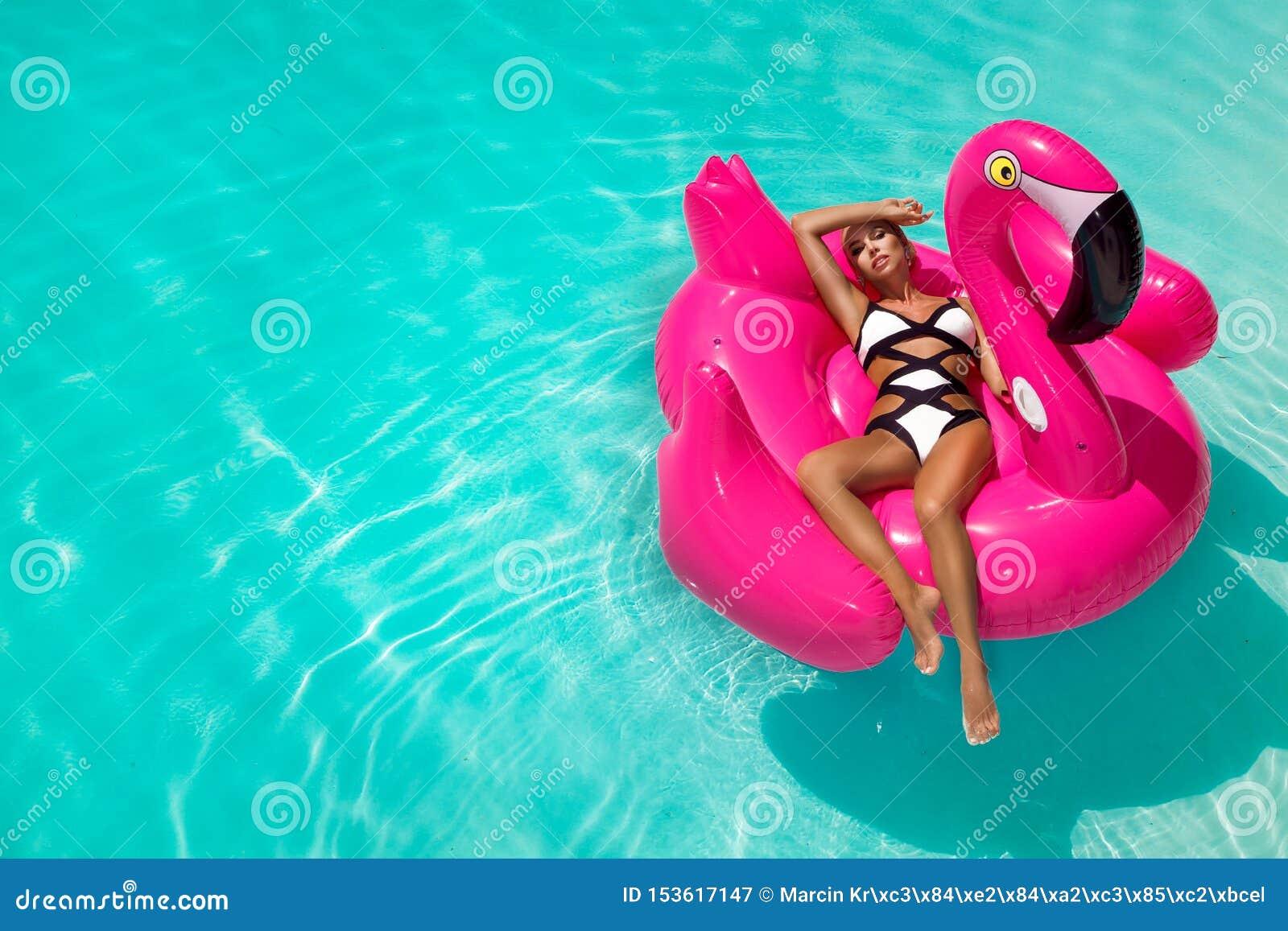 Schöne sexy, erstaunliche junge Frau in einem auf einem aufblasbaren rosa lodernden sitzenden und lachenden Swimmingpool, gebräun