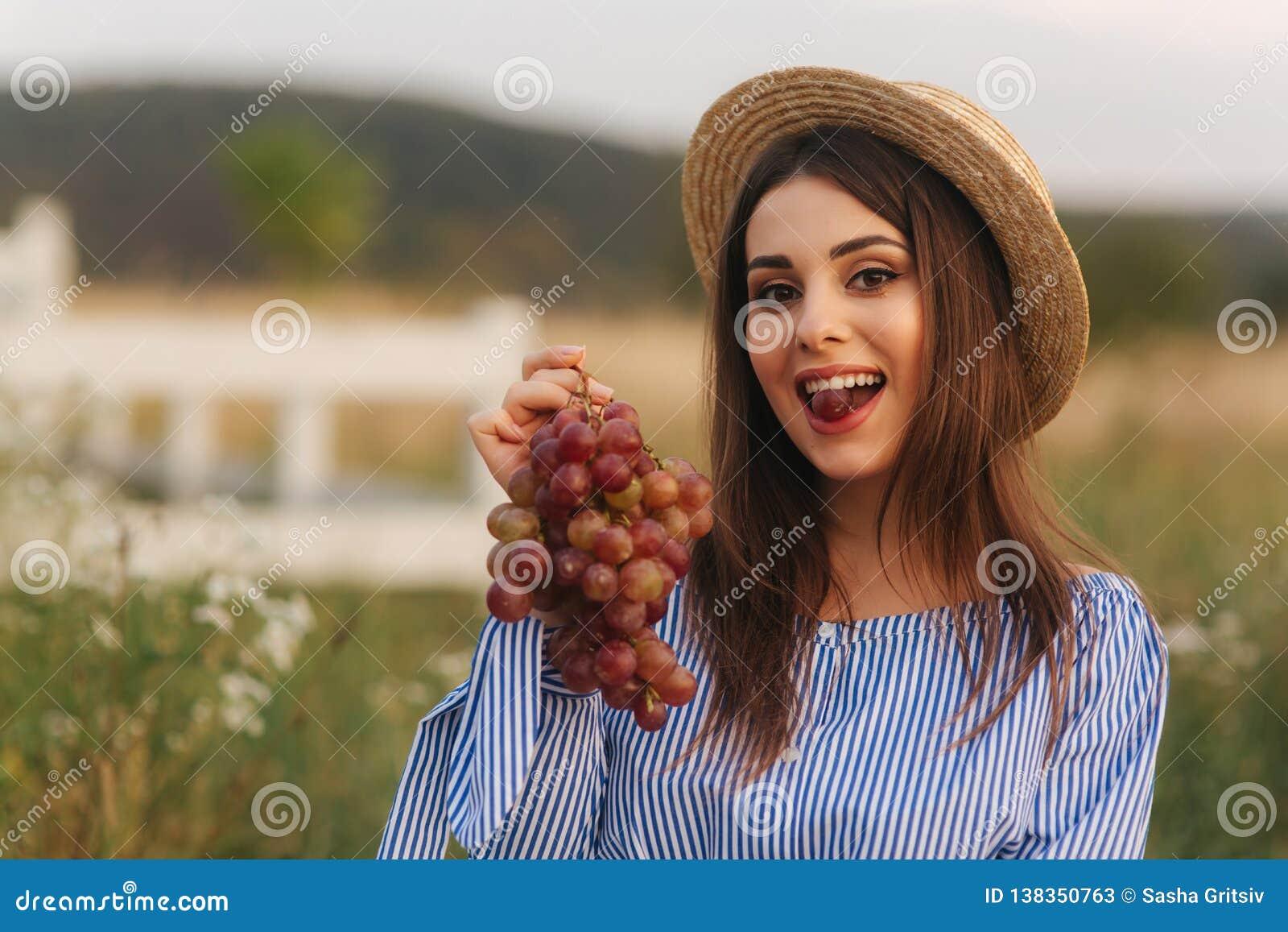 Schöne Show der schwangeren Frau und rote Trauben essen Gesunde Nahrung Frische Früchte Glückliches Frauenlächeln