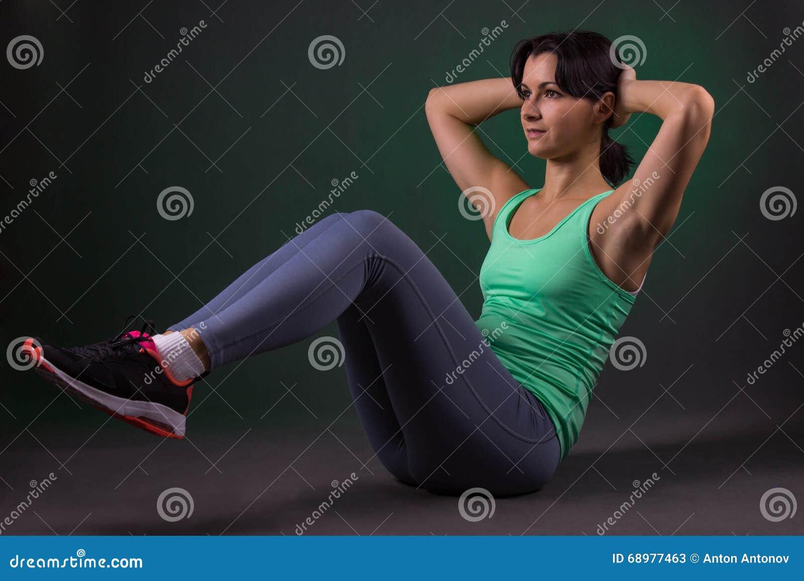 Schöne sportliche Frau, Eignungsfrau, die Übung auf einem dunklen Hintergrund mit grüner Hintergrundbeleuchtung tut