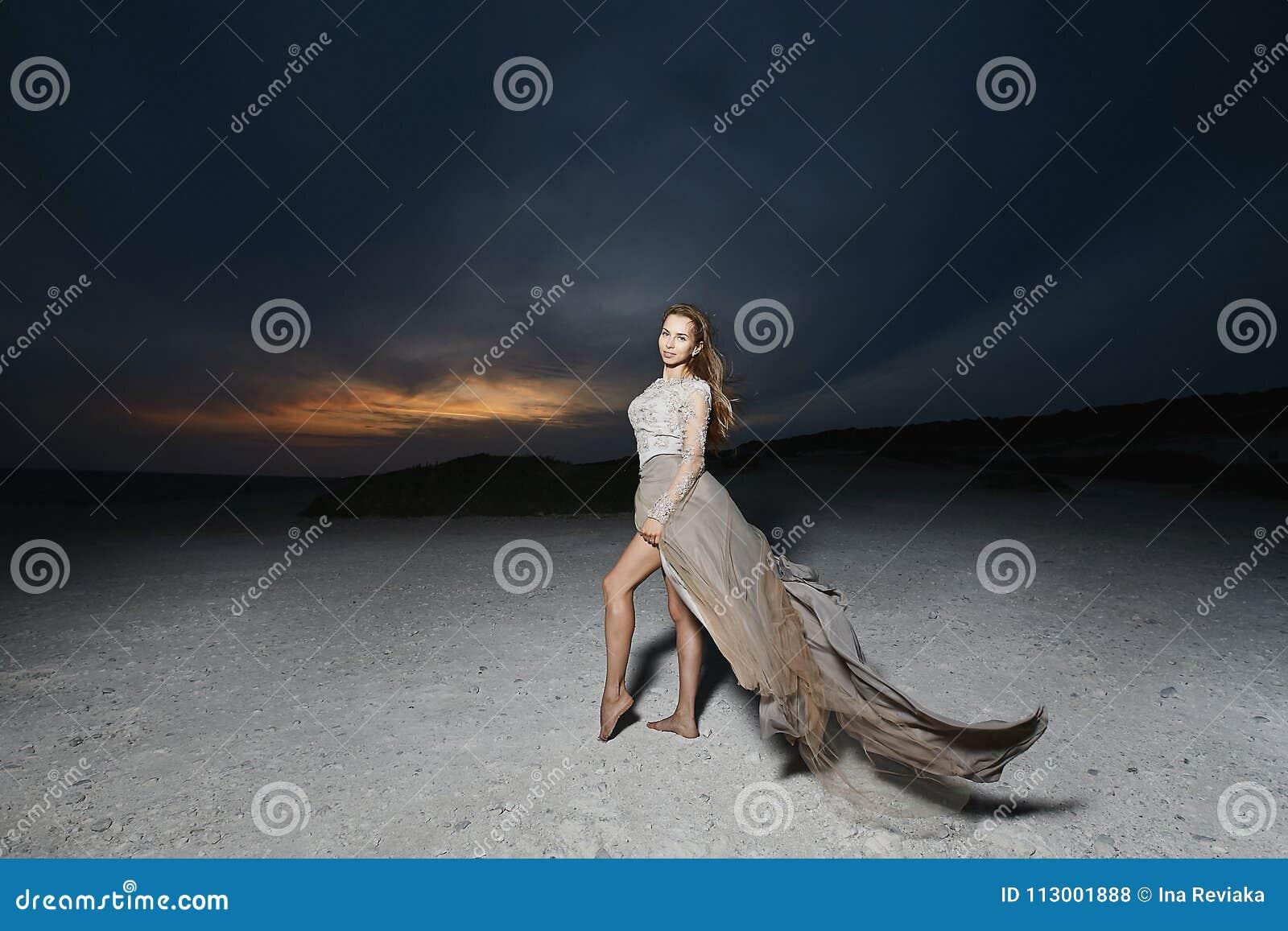 Schöne und junge Brunettemodellfrau, im beige Spitzekleid, werfend bei dem Sonnenuntergang auf