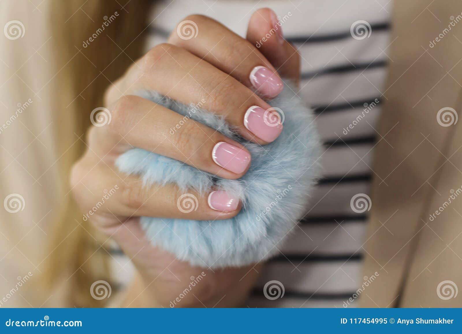 Schöne weibliche Hand mit Maniküre hält einen blauen flaumigen Ball Empfindlicher rosa Nagellack mit weißem crescentsand und wohl