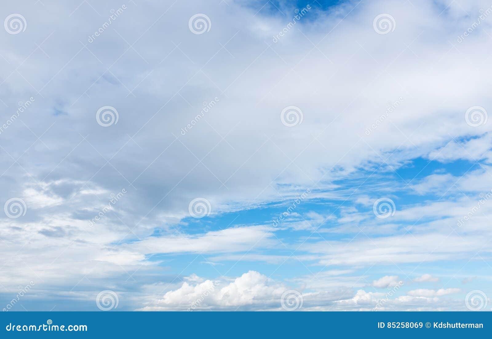 Schöner blauer Himmel mit bewölktem Feld des grünen Grases gegen einen blauen Himmel mit wispy weißen Wolken draußen