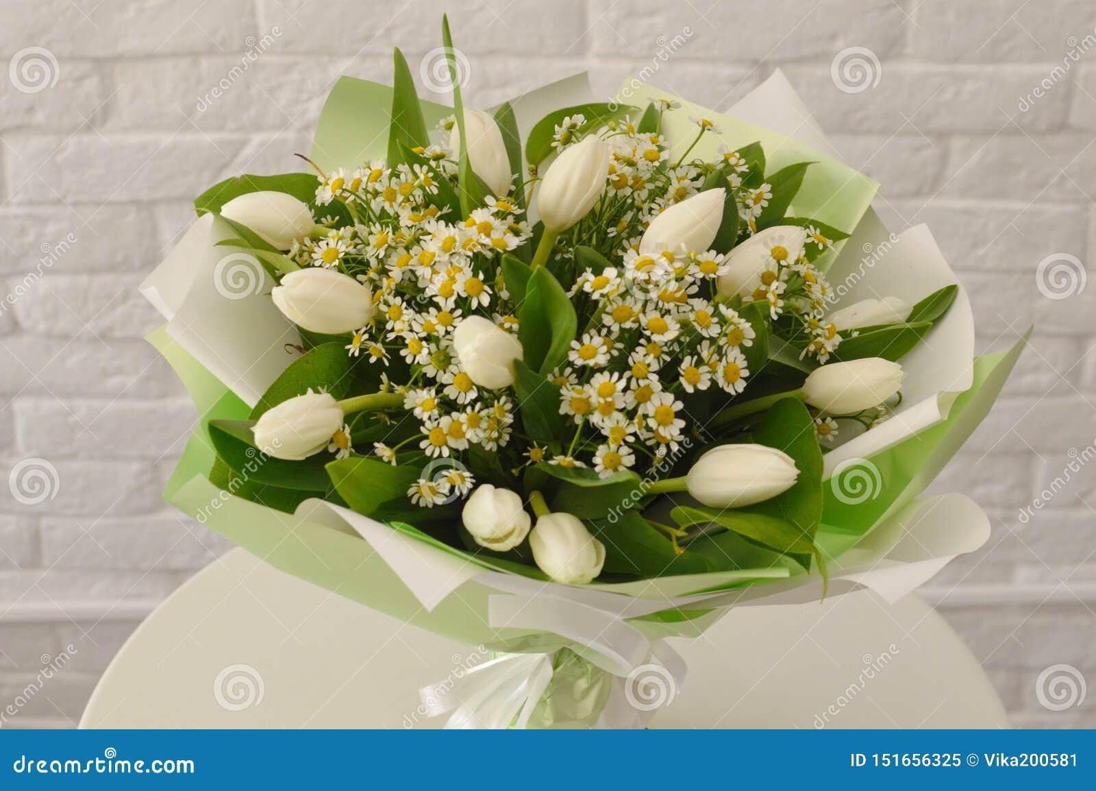 Schöner Blumenstrauß mit weißen Tulpen und camomiles
