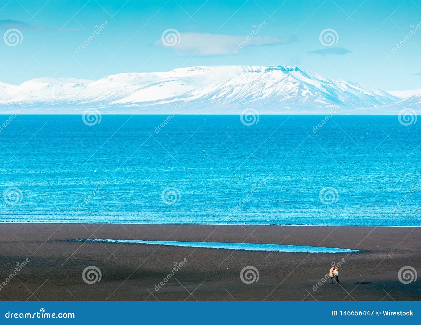 Schöner breiter Schuss des Meeres mit überraschendem weißem Berg im Hintergrund