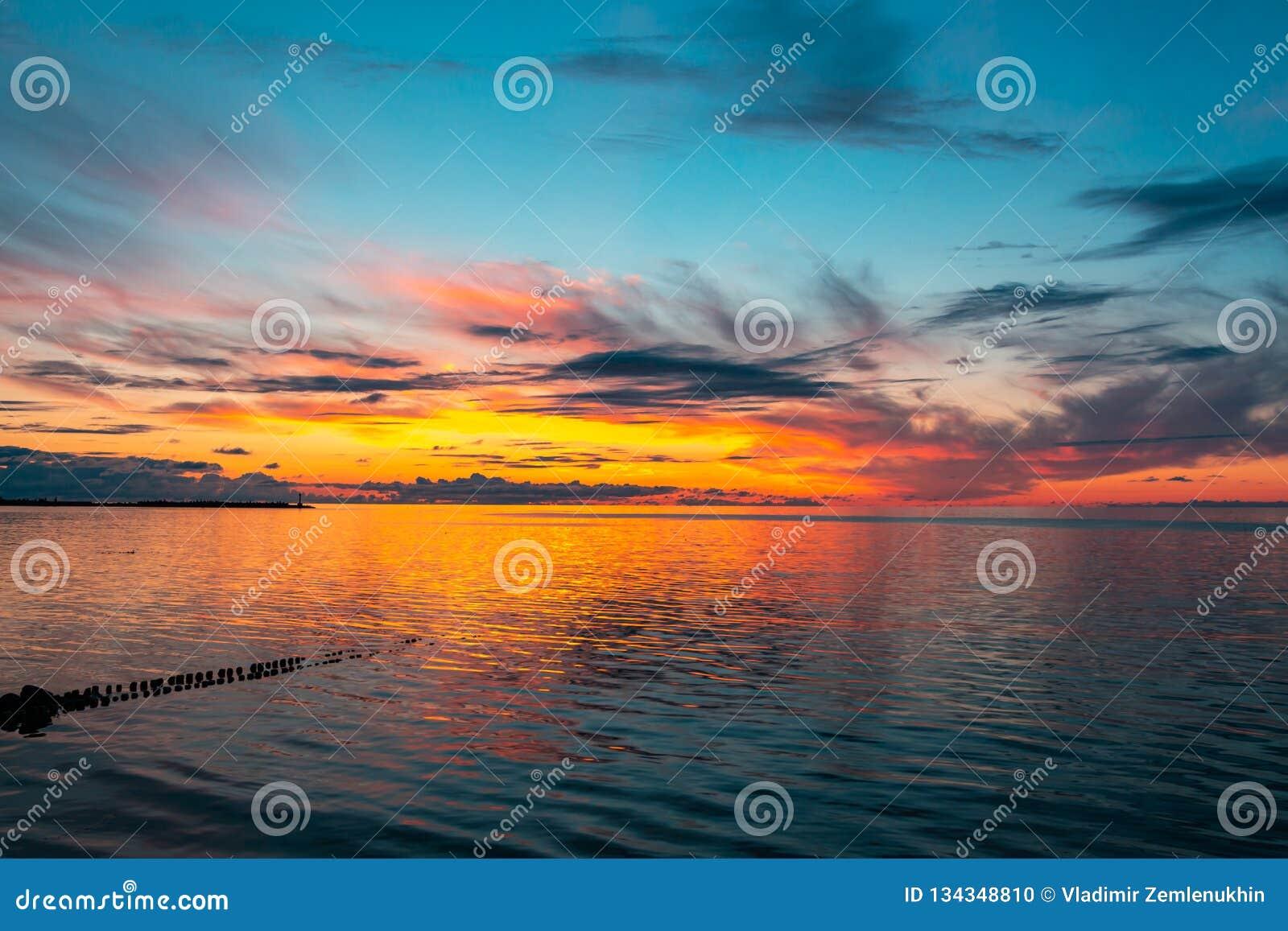 Schöner brennender Sonnenunterganghimmel auf dem Strand
