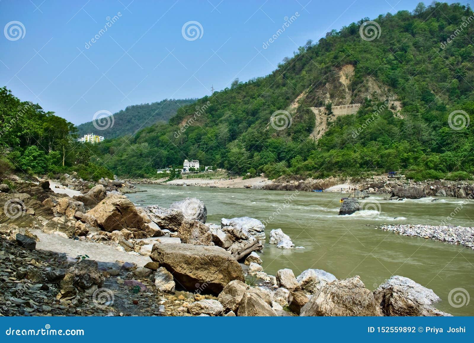 Schöner Fluss mit Bergen im Hintergrund und bunten Häusern in den Seiten des Flusses Rishikesh eine schöne Stadt in Indi